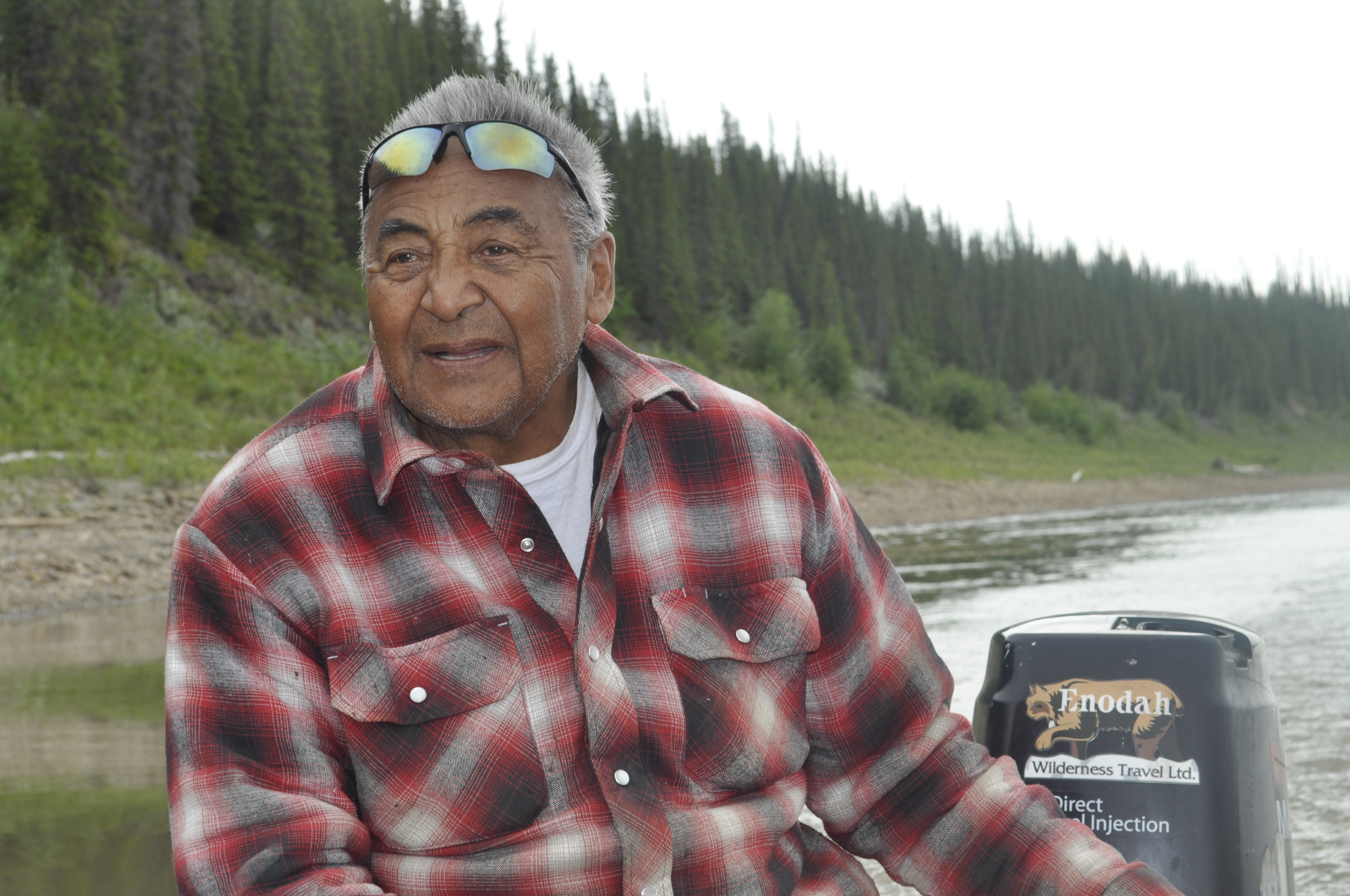 Wilfred Jackson steers his boat on the Mackenzie River. He's spent most of the past 80 summers on the river and knows how it's been changing. (Alex Brockman/CBC)