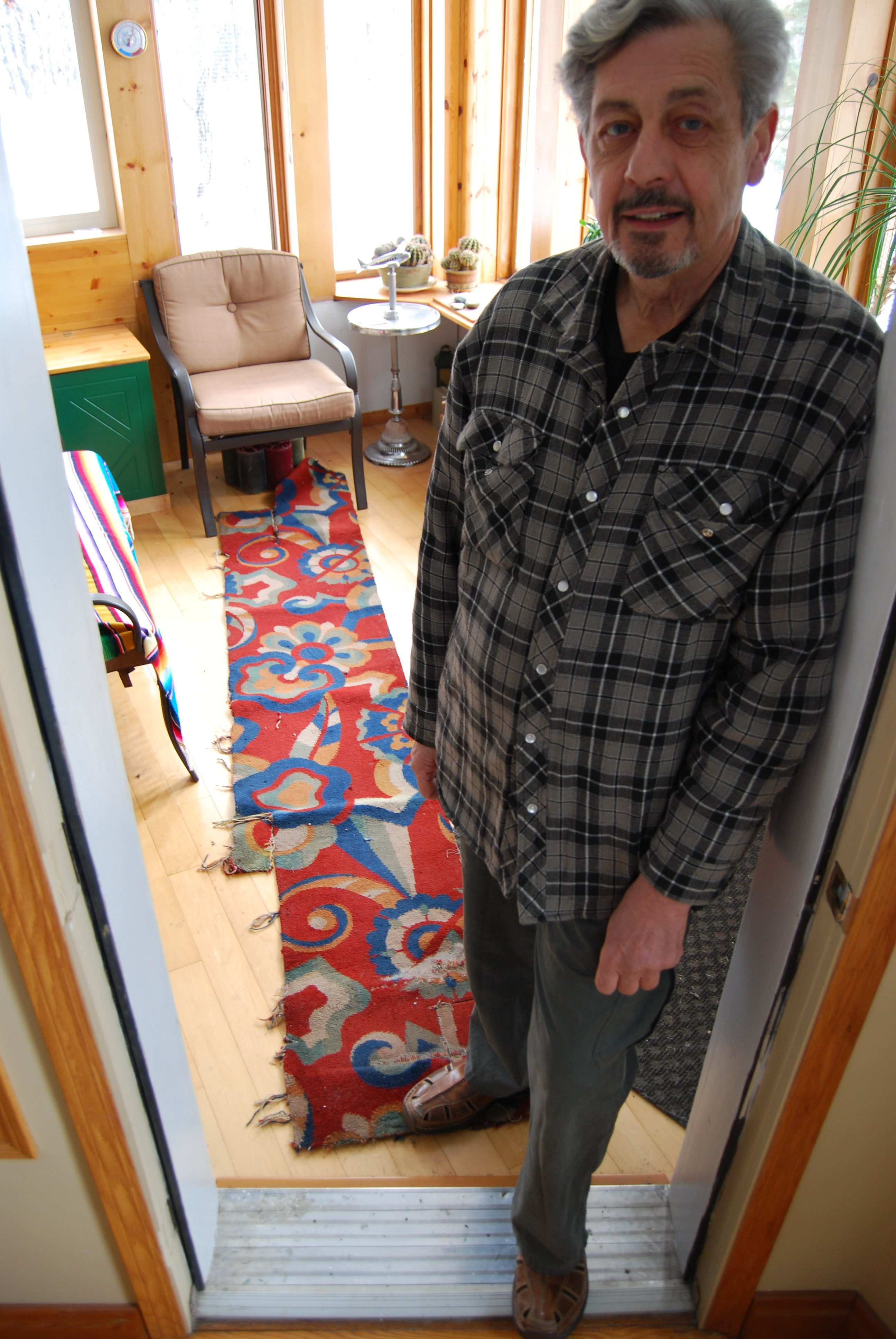 Saskatoon-area resident Richard Perry, pictured here in 2019, with a piece of Capitol carpeting he salvaged during the demolition of 1979. (Guy Quenneville/CBC)