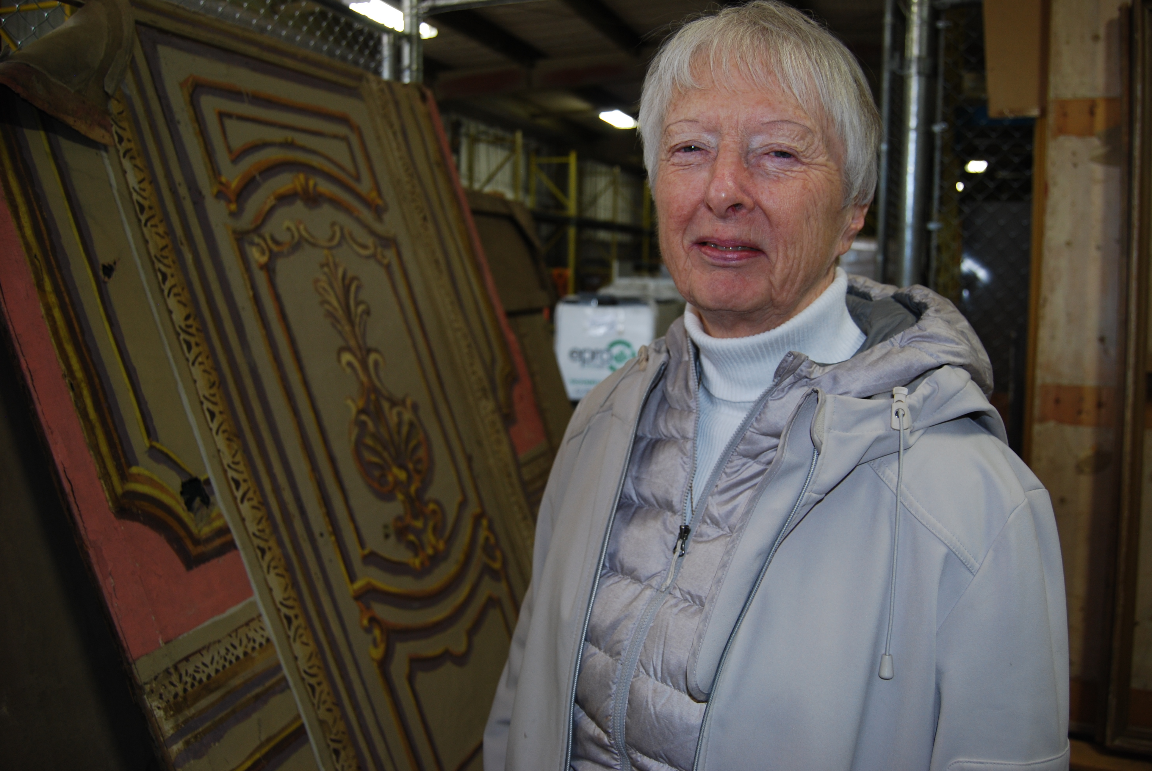 Peggy Sarjeant, the president of the Saskatoon Heritage Society, stands inside the city warehouse where dozens of Capitol relics continue to be stored. She'd like all the artifacts, including those secretly salvaged by people during the demolition, to be on display in a public space. (Guy Quenneville/CBC)