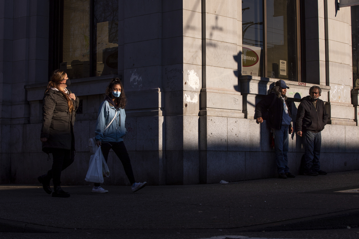 People wearing face masks walk near Main and Hastings streets in the Downtown Eastside neighbourhood of Vancouver on Dec. 4, 2020. (Ben Nelms/CBC Vancouver)