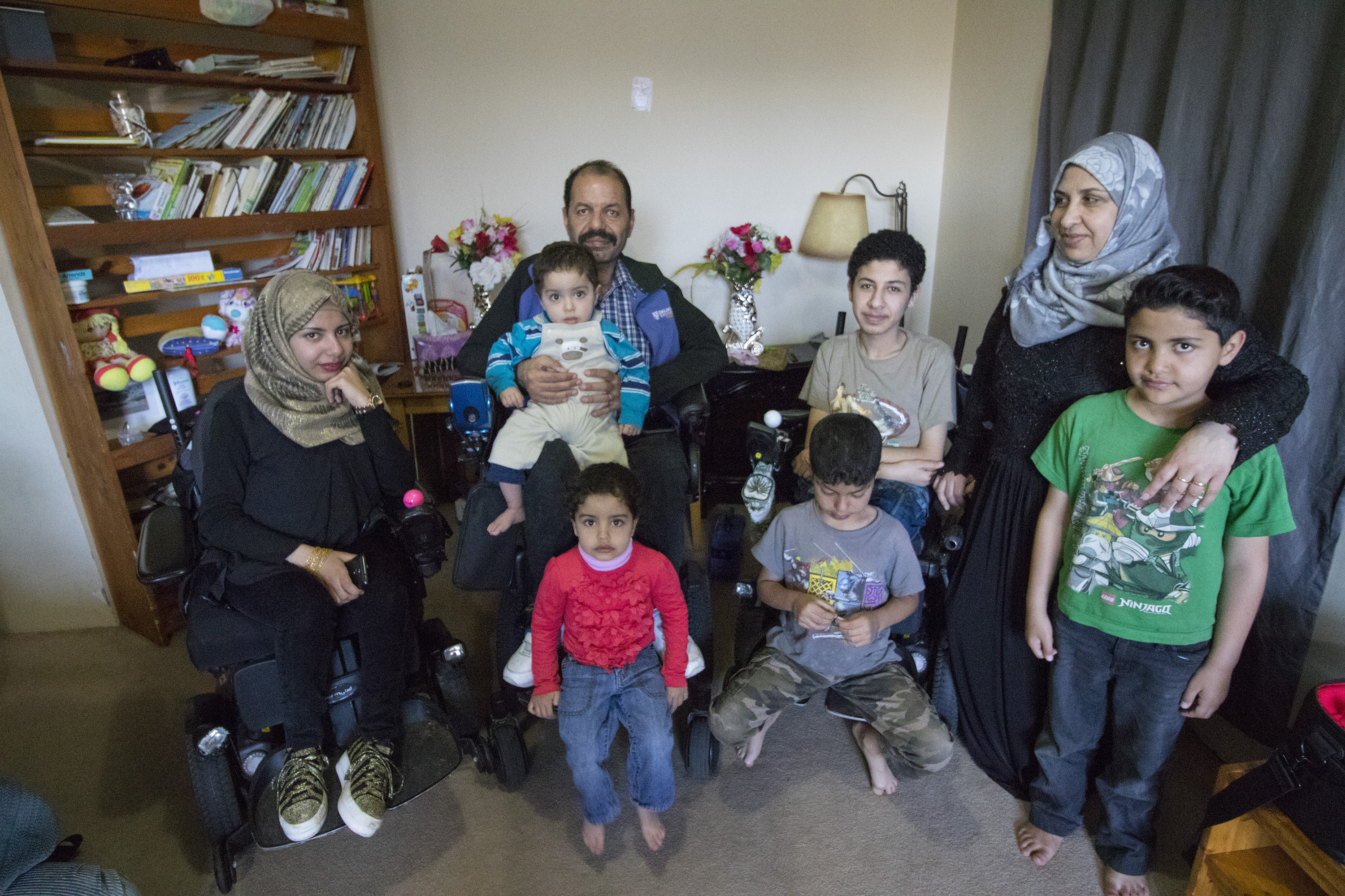 Eight members of the Harb family together in their living room. (Dave Irish/CBC)