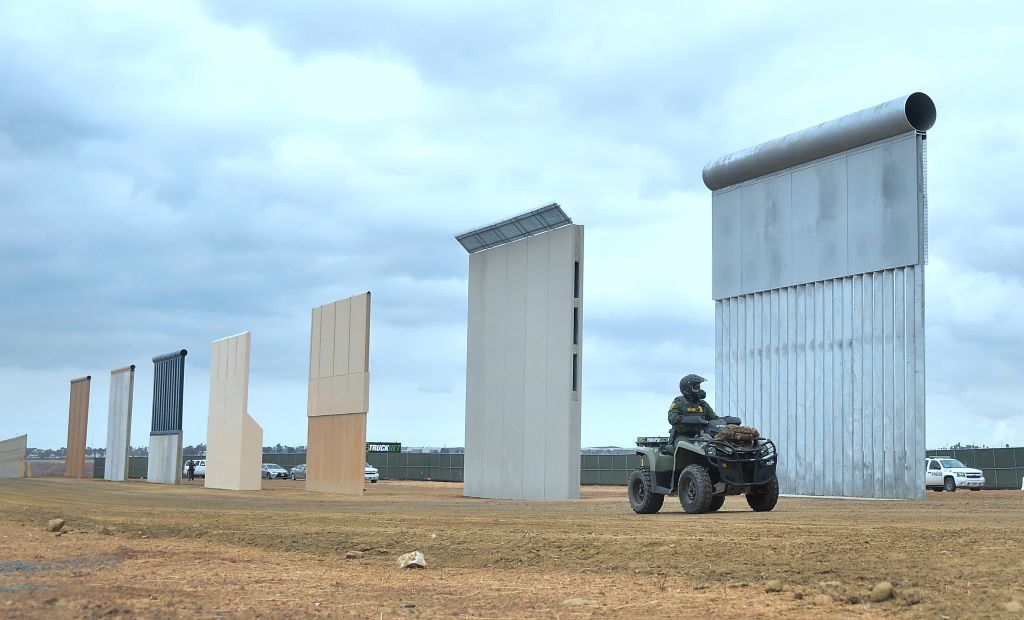 A U.S. Homeland Security border patrol officer rides an ATV past prototypes of President Donald Trump's proposed border wall, on November 1, 2017, in San Diego, California. (Frederic J. Brown/AFP/Getty Images)