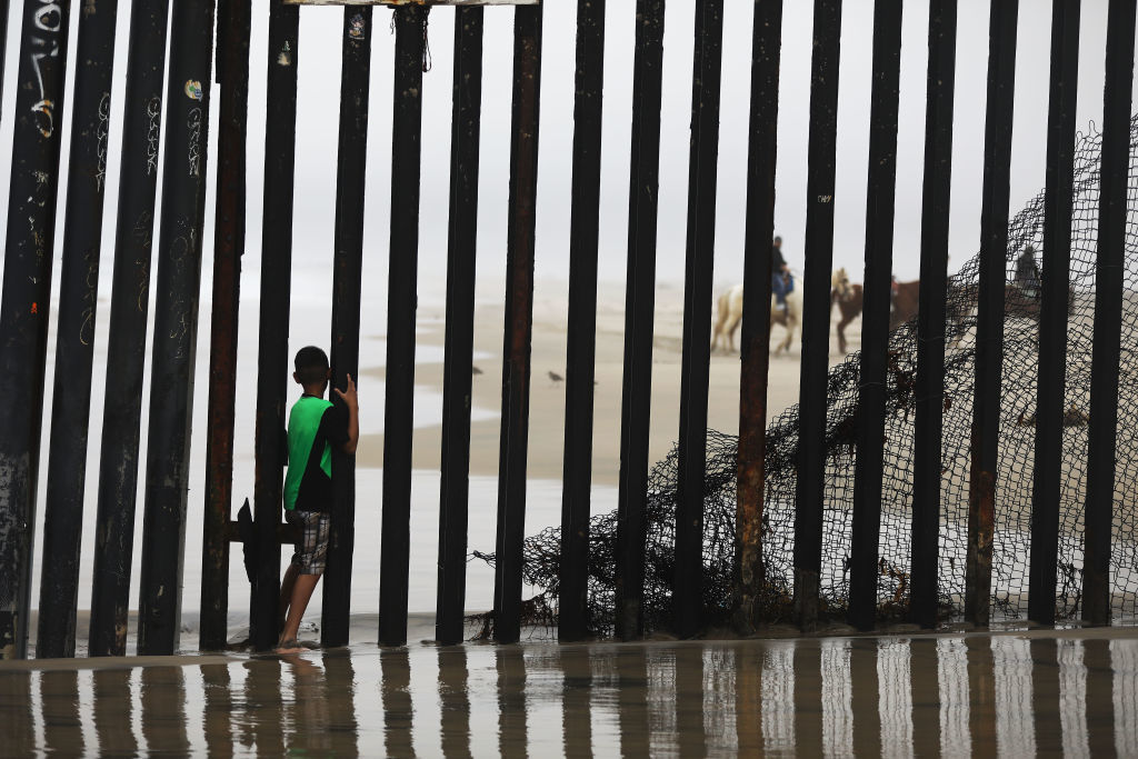A boy stands between posts in the U.S.-Mexico border fence, with people riding horses visible on the American side, on a beach in Tijuana, Mexico, on March 9, 2018. (Mario Tama/Getty Images)