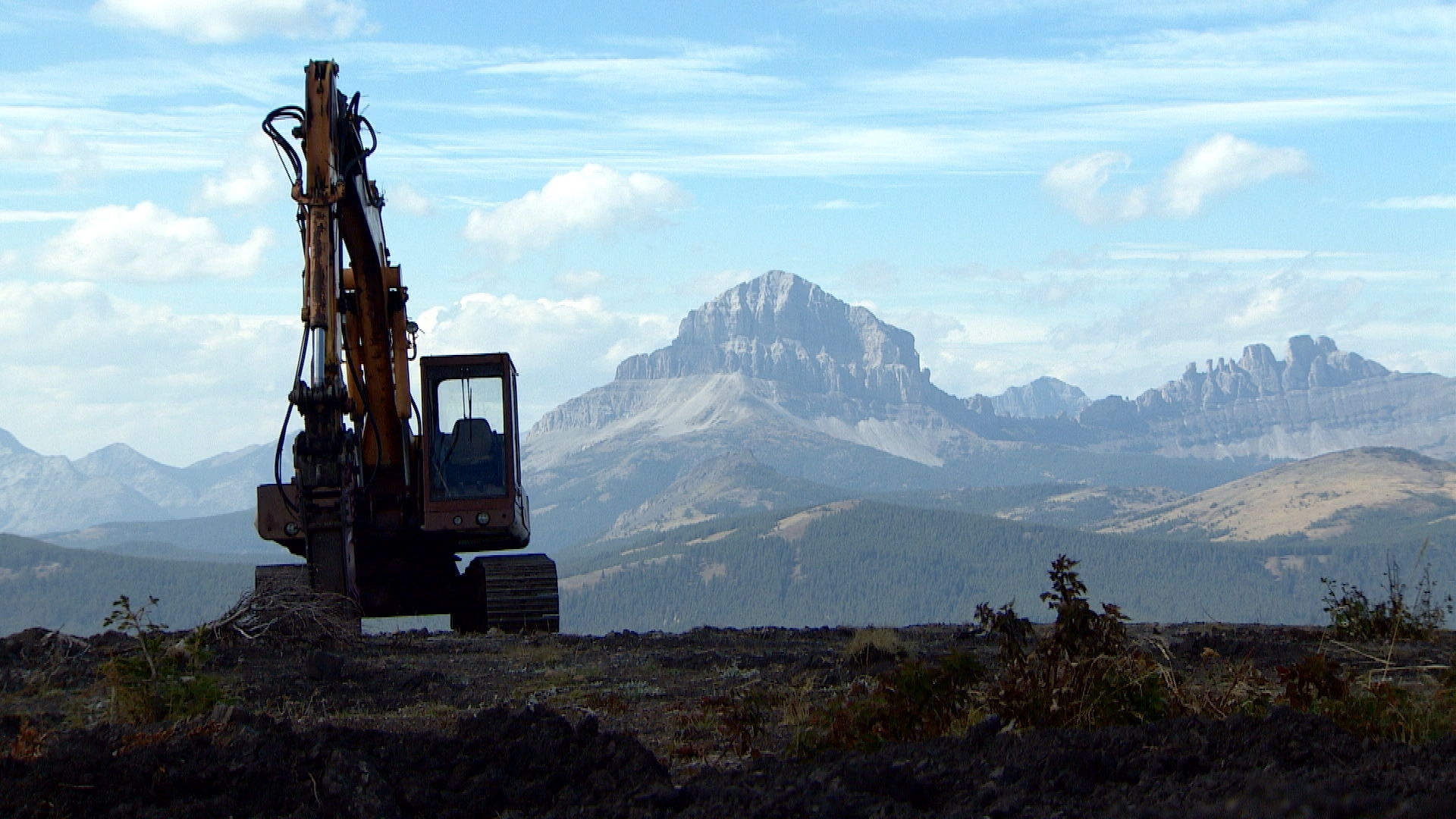 Construction equipment near Grassy Mountain in 2014, with the distinctive peak of Crowsnest Mountain in the background. (CBC)