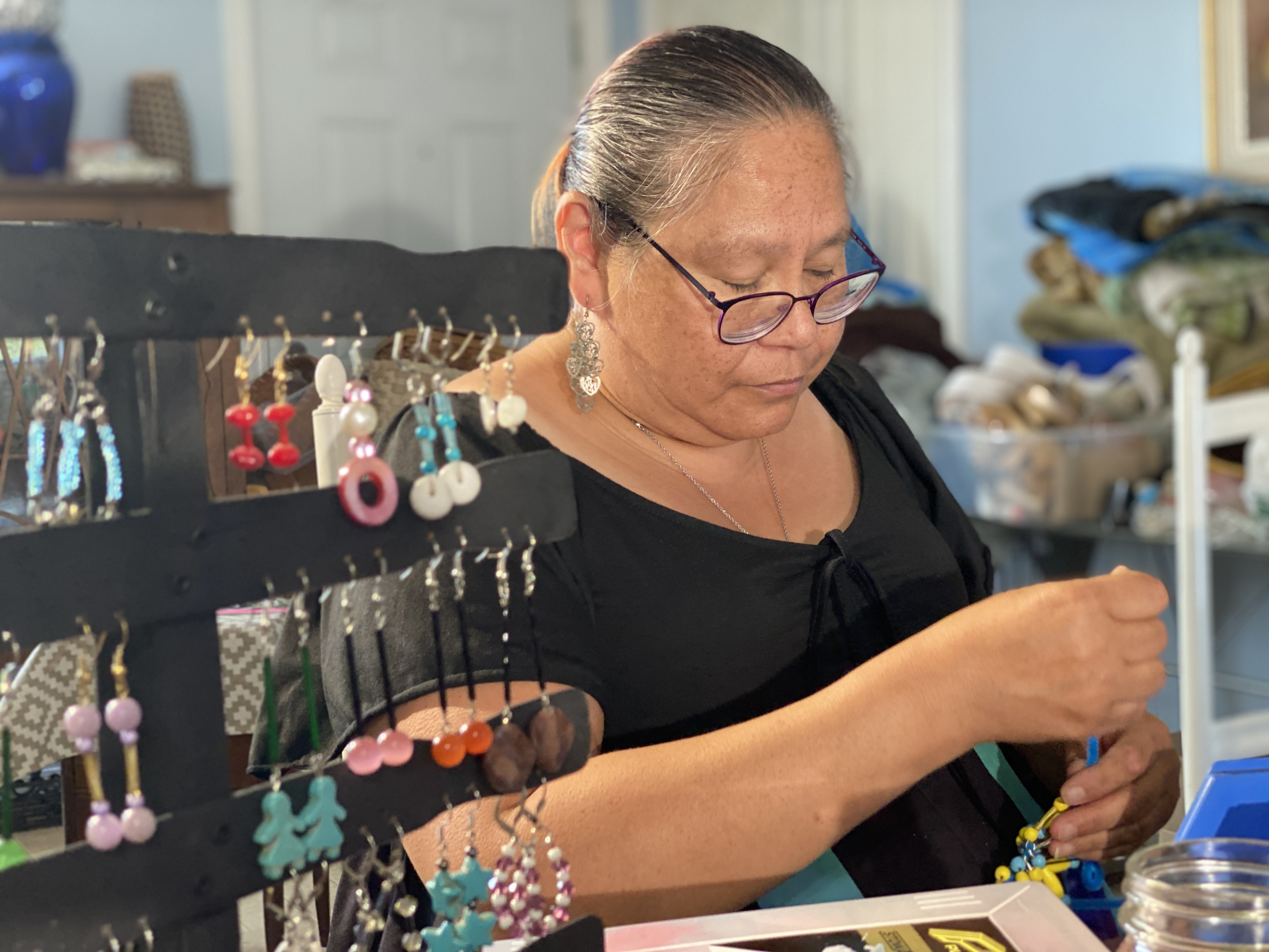 For Patsy Gavin, shown making jewelry at her home on Lennox Island, talking about her school days is anything but nostalgic. She recalls years of fear and abuse. (Kirk Pennell/CBC)