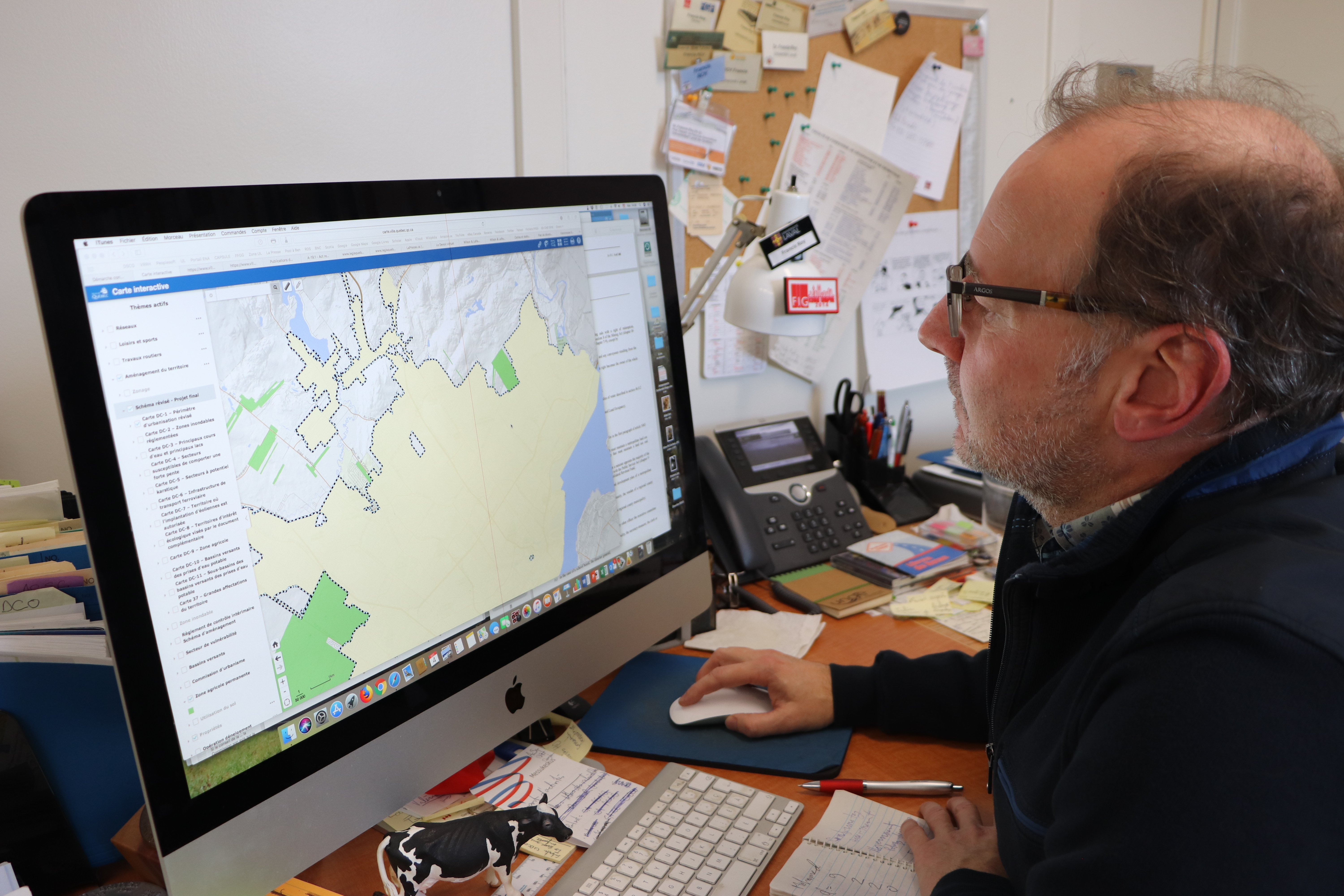 Professor Francis Roy looks at the new land use plan the Quebec City Agglomeration Council hopes to see approved by the province. (Julia Page/CBC)