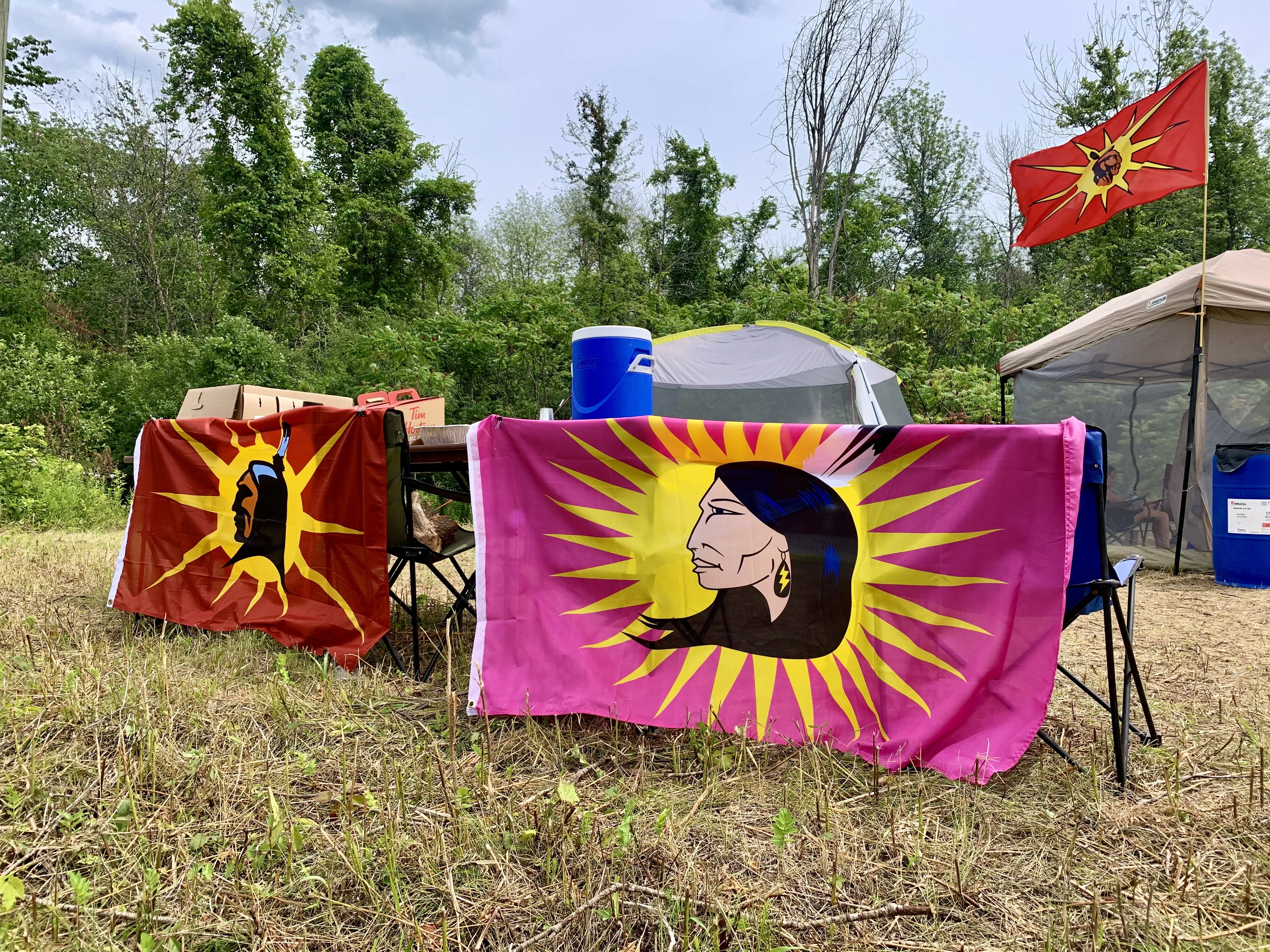 The main camp is located on Parcel E, an area of land that was returned to Kahnawake in 2018, while smaller camps are scattered across the adjacent property that is being reclaimed to prevent a housing development project. (Ka'nhehsí:io Deer/CBC)
