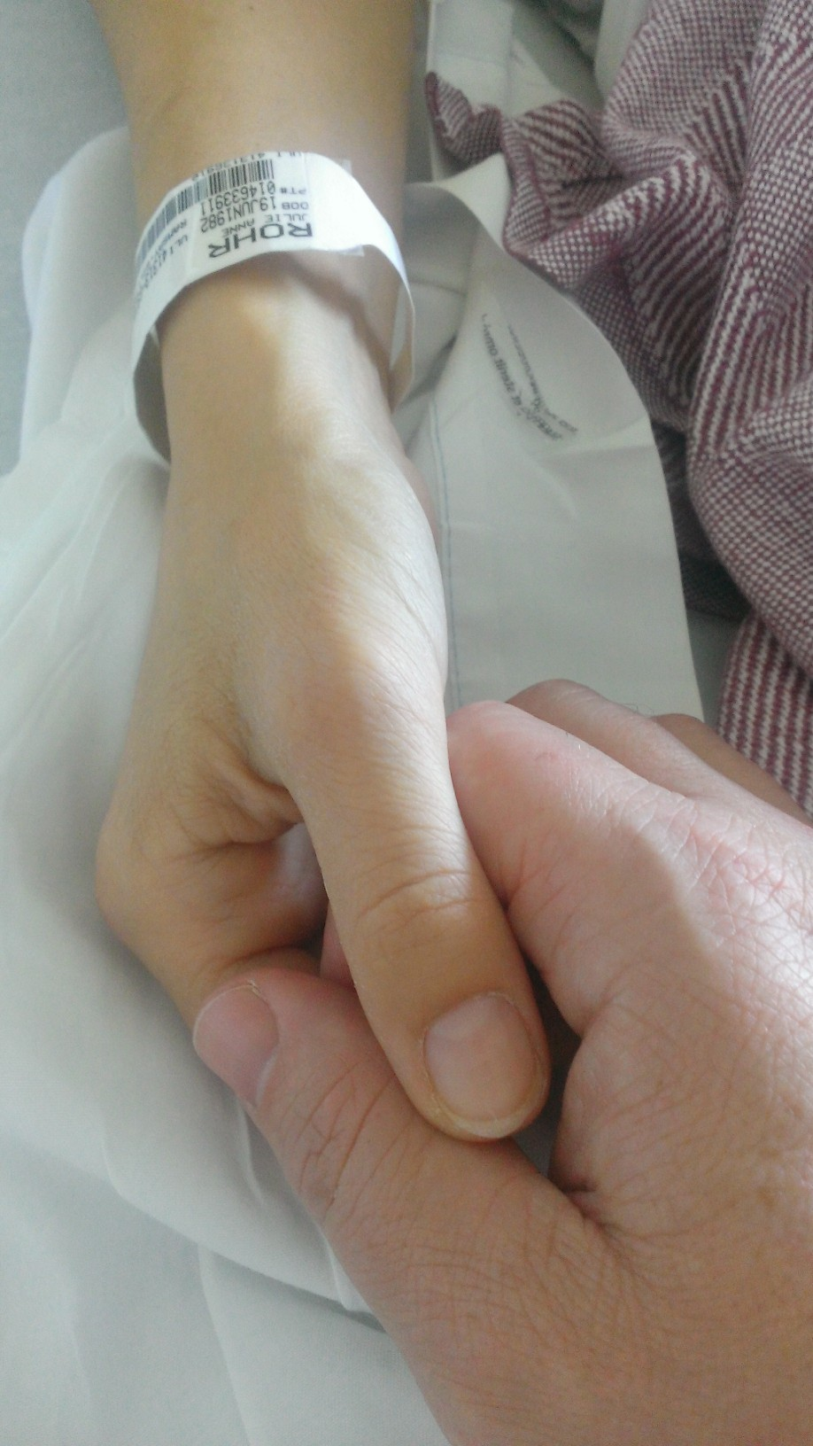 Julie Rohr holds her husband David's hand while in hospital. (David Schoor)