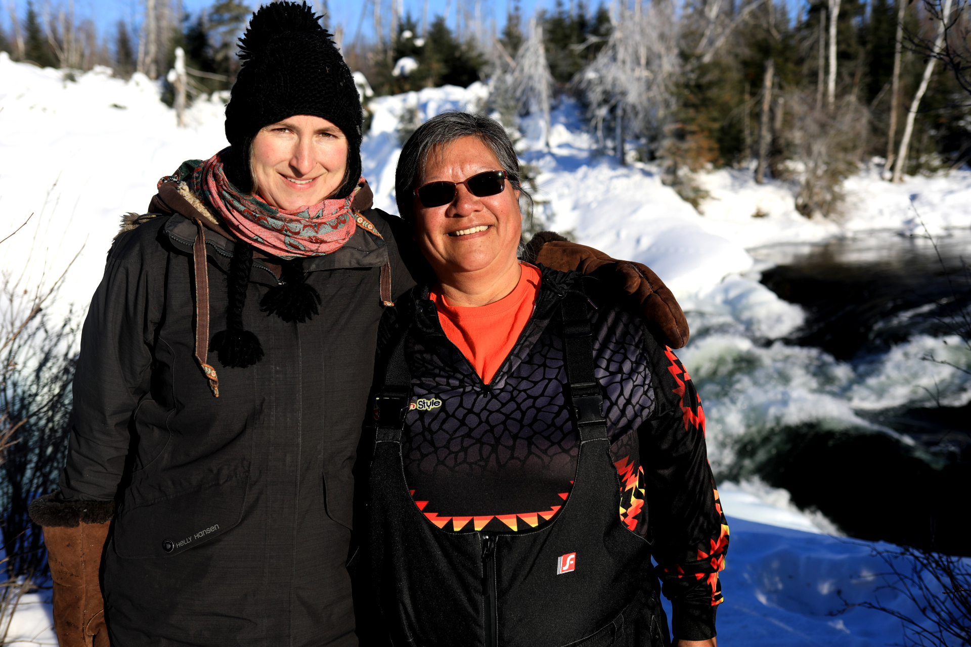 Eliza Doyle and Isabelle Hardlotte smile at the Nistowiak Falls near Stanley Mission. (Heidi Atter/CBC)