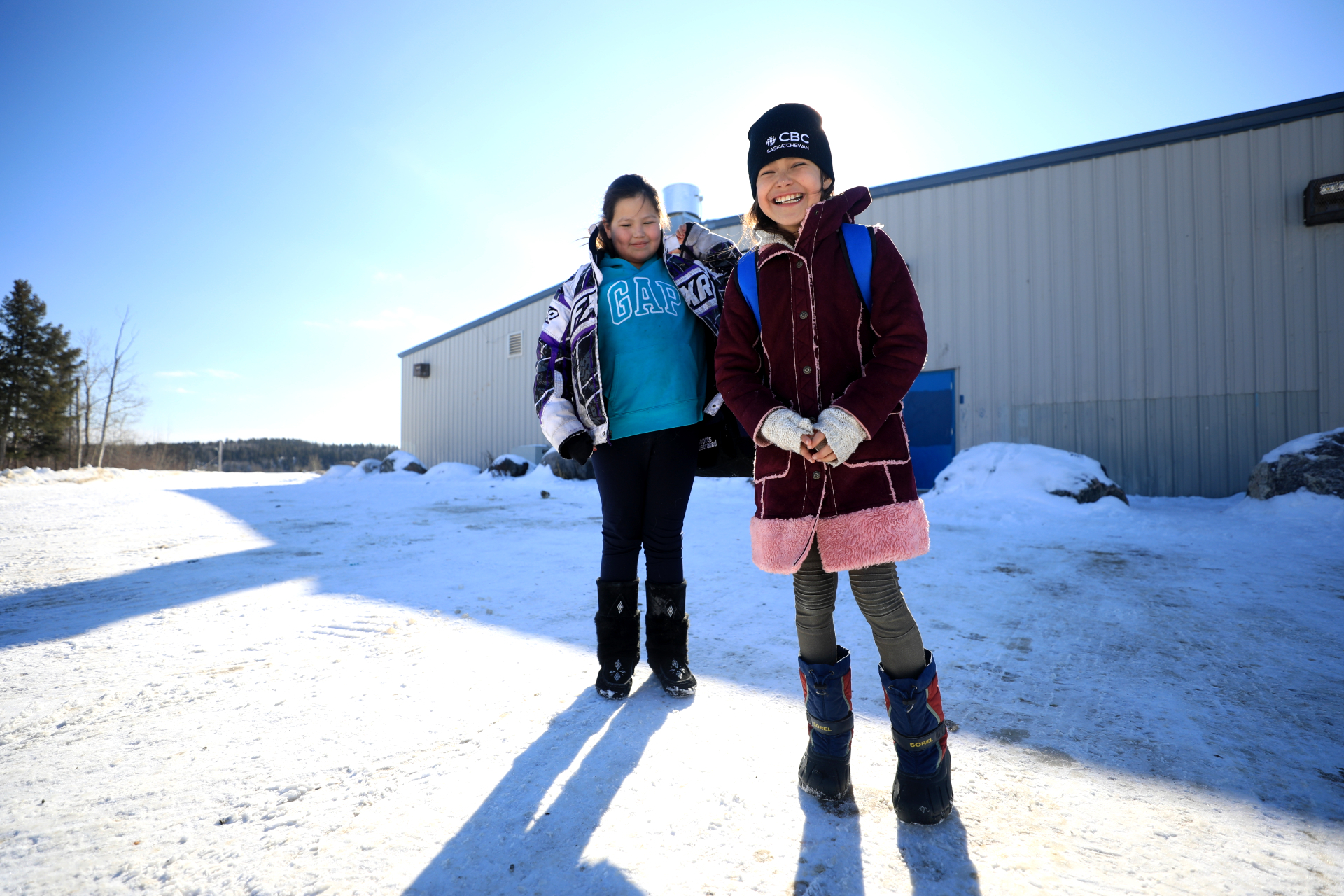 Two girls chat about the DSLR camera while waiting to go into the ice skating rink in Stanley Mission in March, 2020. (Heidi Atter/CBC)