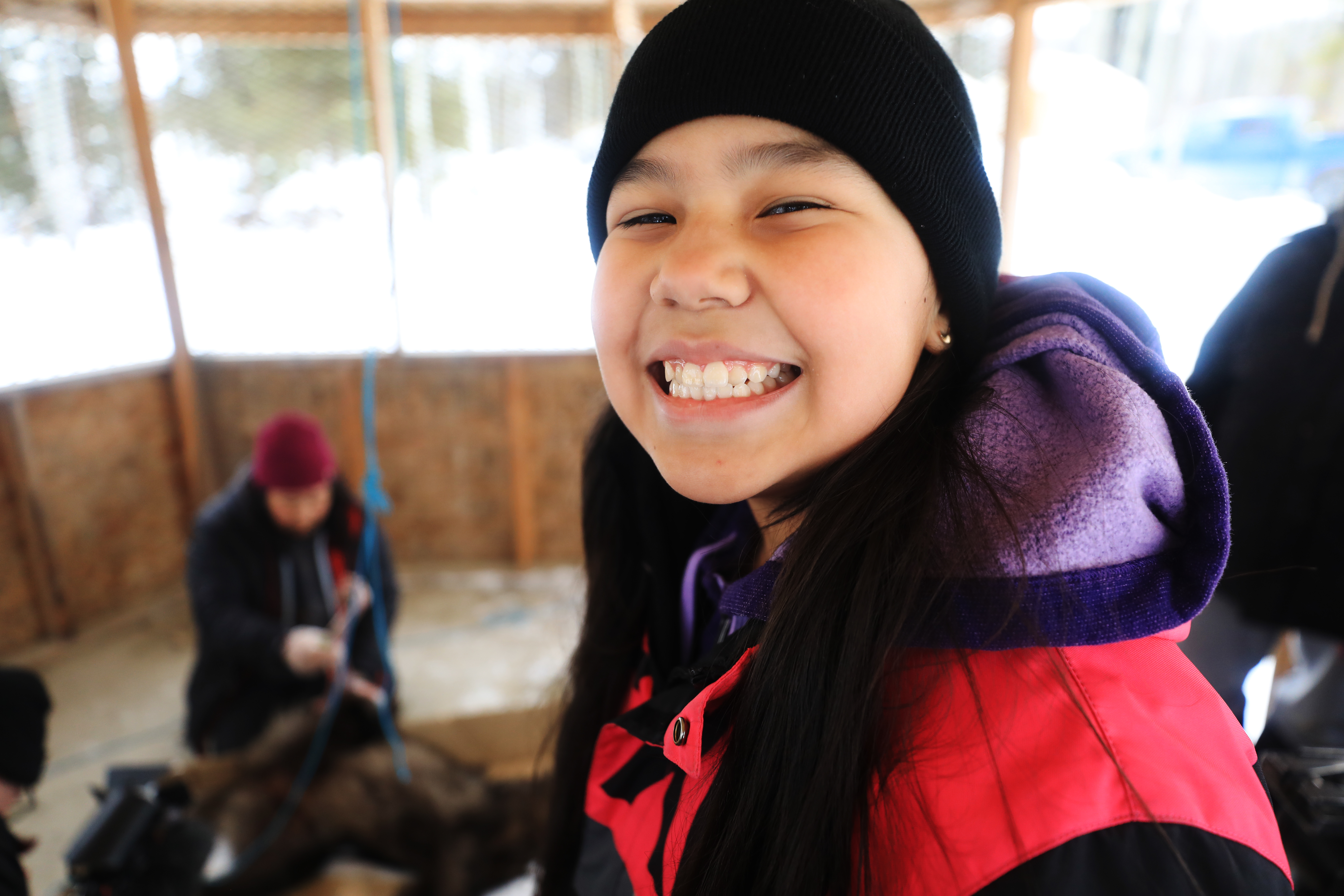 A Grade 4 student smiles for a snapshot during the wolf-skinning demonstration. (Heidi Atter/CBC)