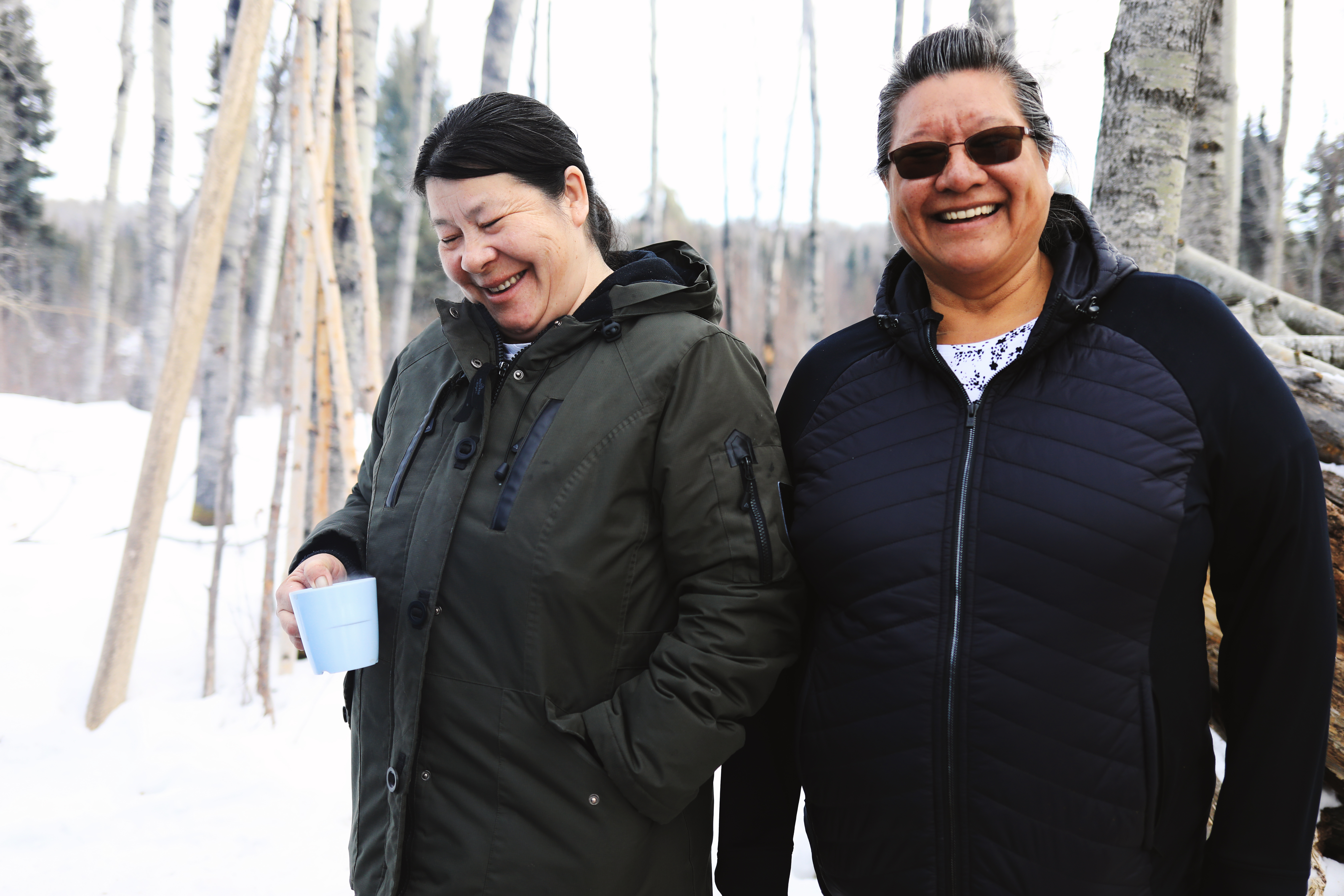 Susan McLeod and Isabelle Hardlotte share a laugh out at the school system's land-based education site. Hardlotte said she would stay out in nature all day if she could. (Heidi Atter/CBC)