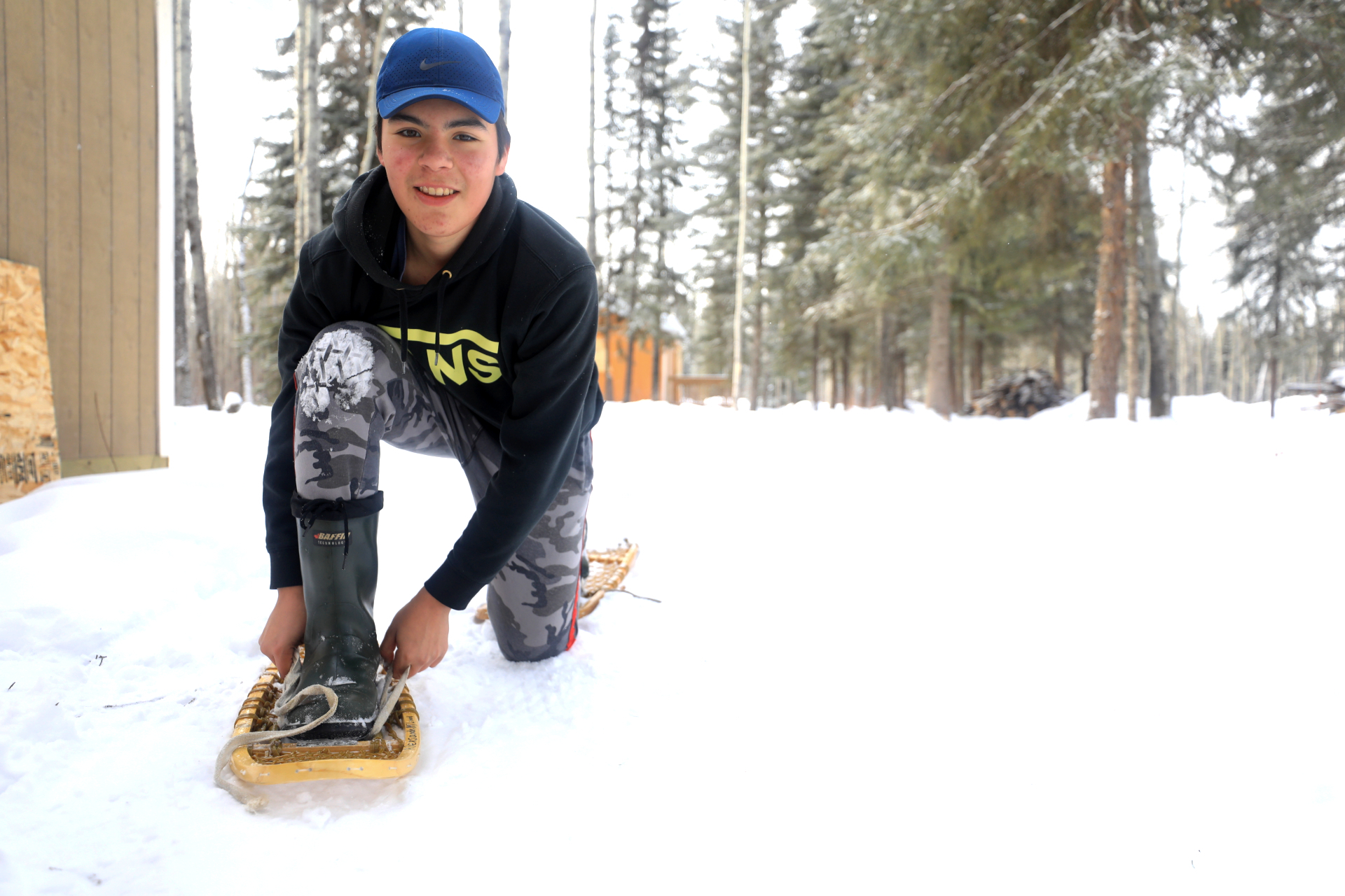 Student Peter Bird ties his snowshoes. (Heidi Atter/CBC)