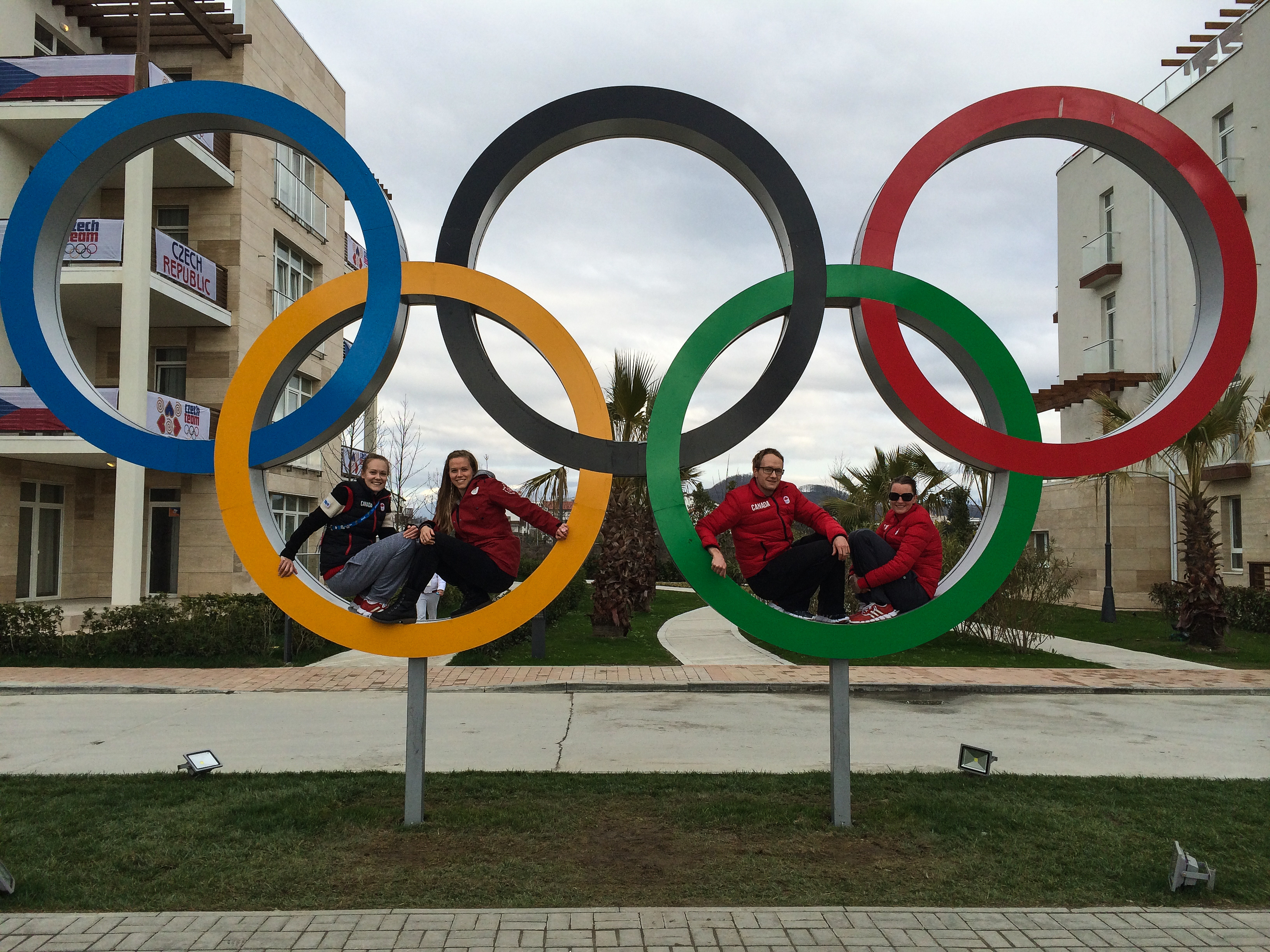 Siblings Jessica Levins, Sarah O'Neill and Jamie Gregg, along with Jamie's wife, Danielle, pose for a photo with the rings in the Sochi athletes village. (Supplied by Kathy Gregg)