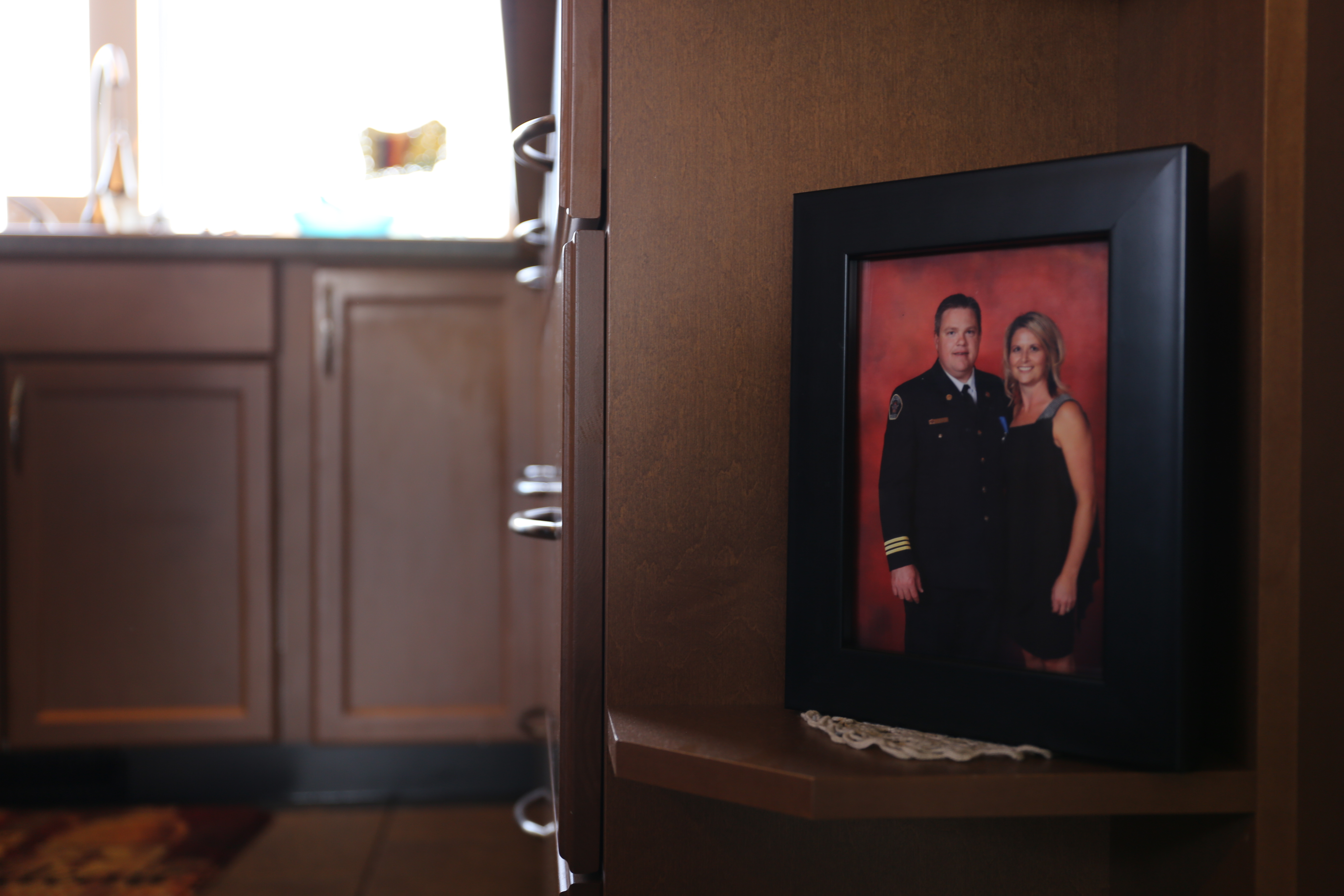 A framed photo of Jody Butz posing in uniform with his wife, sits in his family's kitchen. (Marion Warnica/CBC)