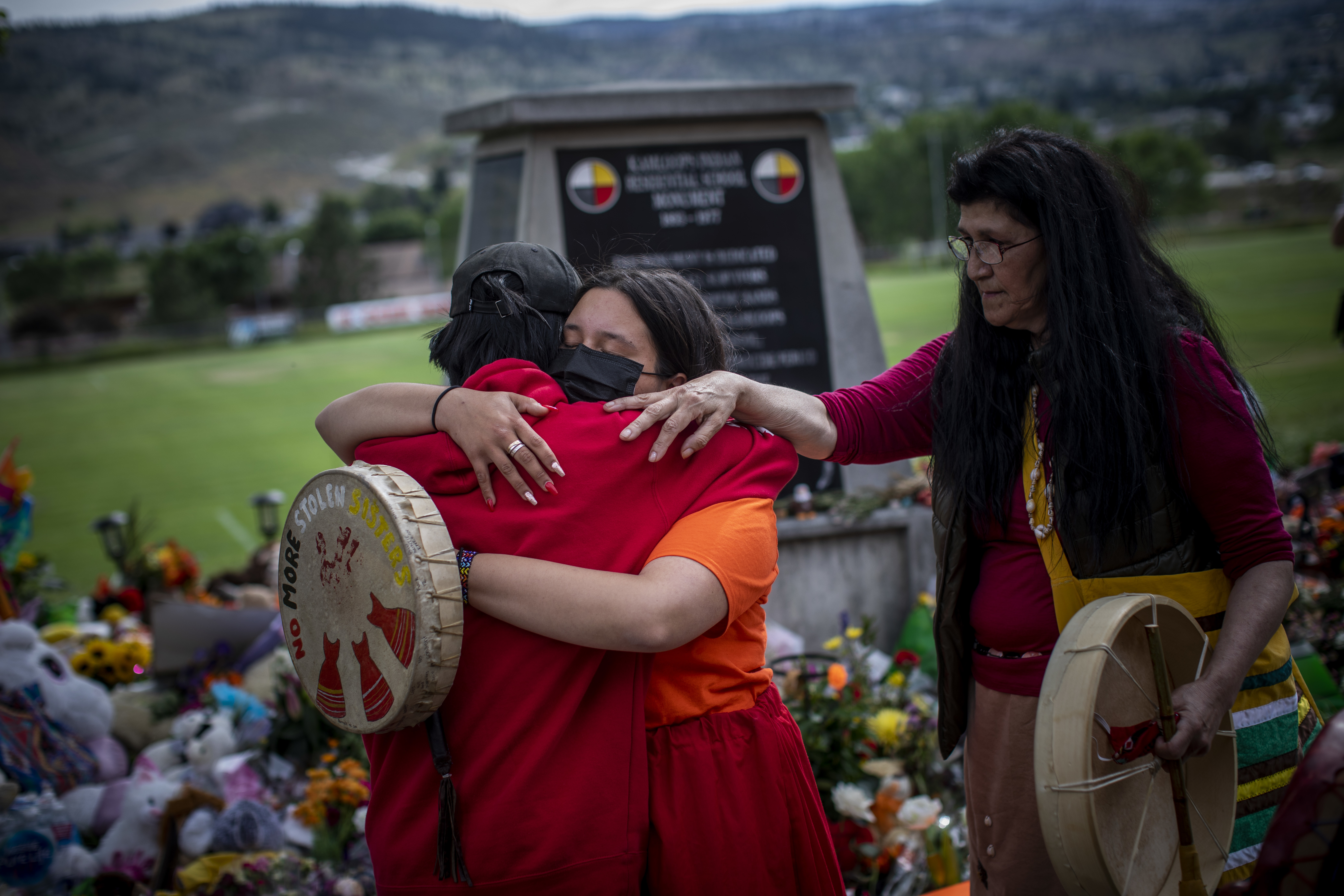 Katherine Cooper, right, from the Mosakahiken Cree Nation in Manitoba consoles her friends at a monument outside the former Kamloops Indian Residential School.