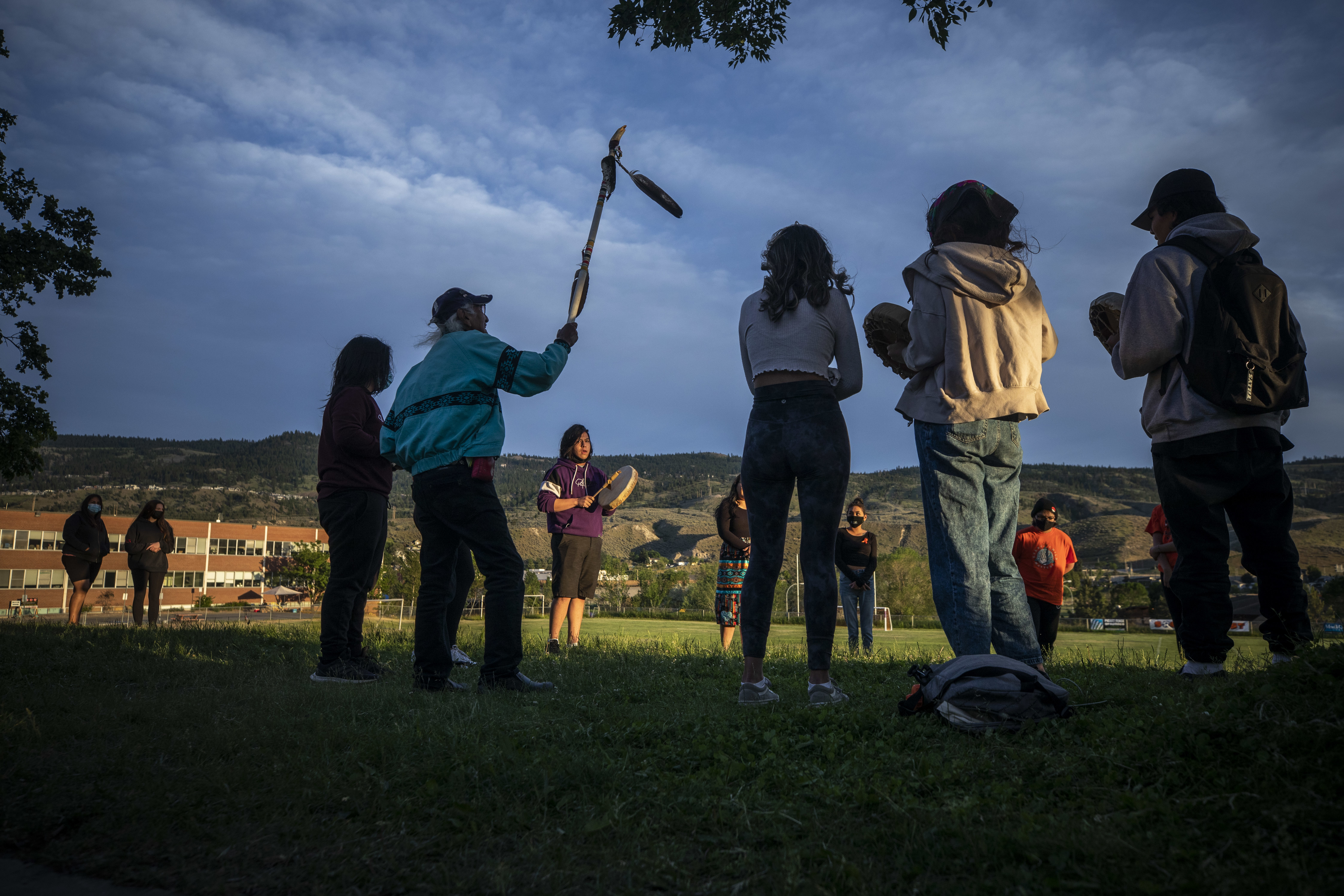 Kamloops Indian Residential School survivor Stanley Paul, 75, who was forced into the school at the age of seven, holds a walking stick in the air while Cash Charters sings and drums with a group of youths at a monument outside the former school.