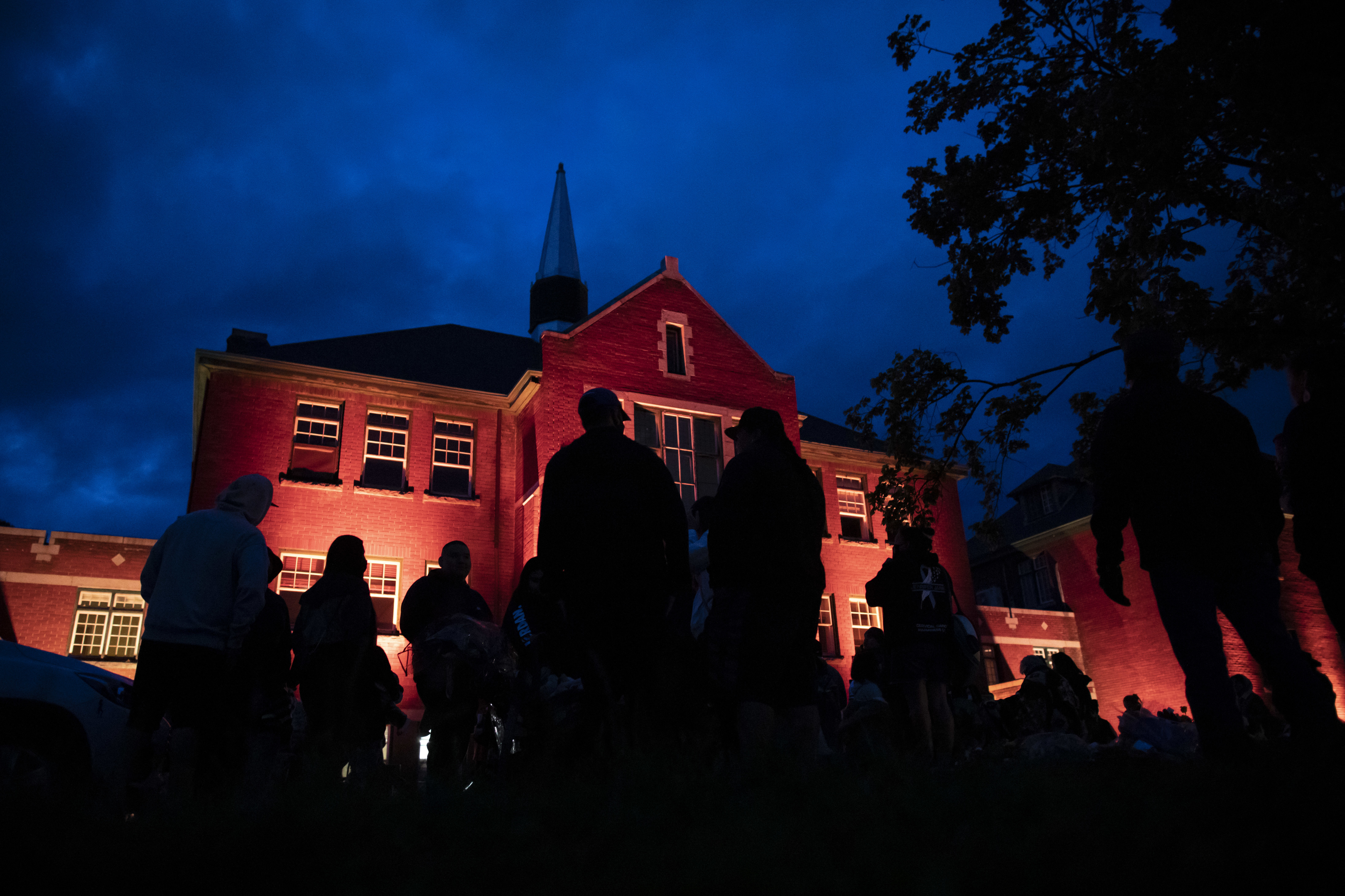 The former school is illuminated with orange lights in the evening as people gather outside the memorial.