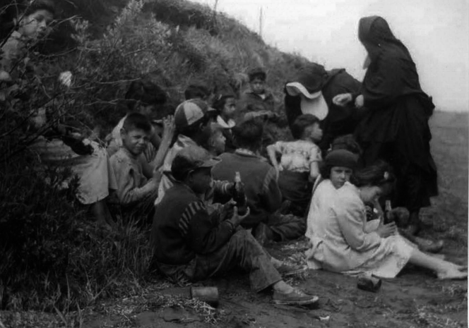 Day school students on a Lennox Island beach, being supervised by two Catholic nuns in habits, in a photo dating back to the 1940s or 1950s. (From the collection of Judy Clark)