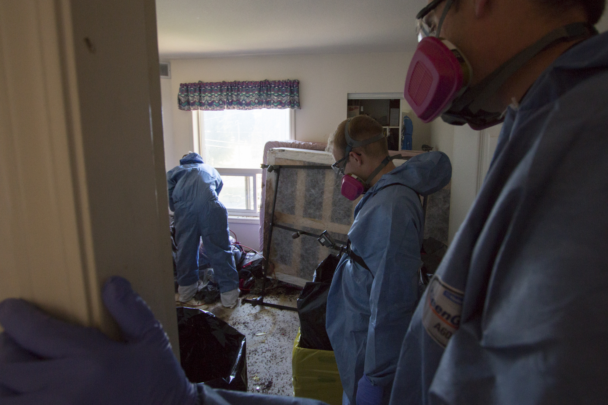 Kreklau and his co-workers look into the bedroom where the deceased was found. Most of the furniture will need to be taken apart and disposed of. (Tina Lovgreen/CBC)