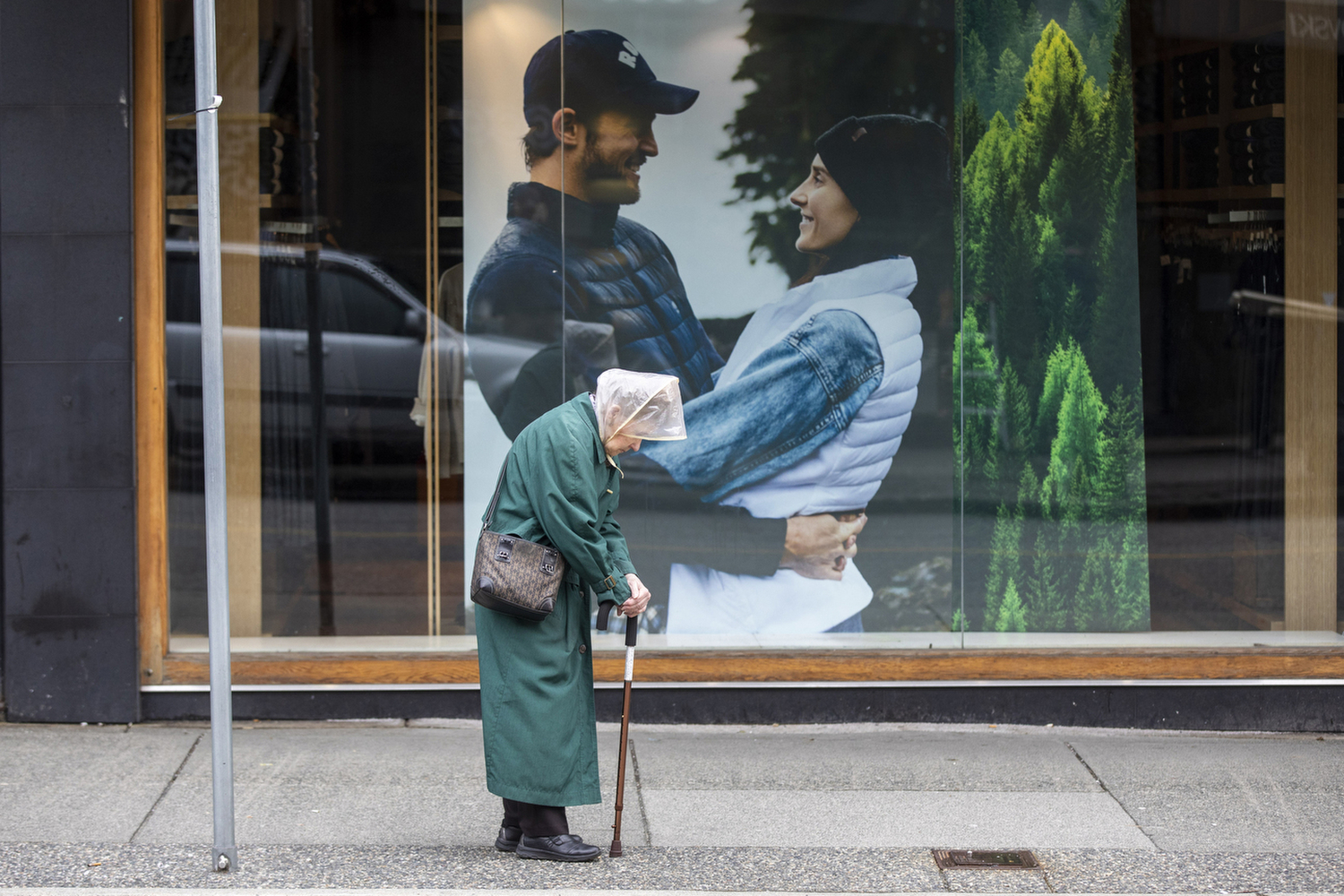 A woman waits for a bus on a near empty Robson Street in downtown Vancouver on March 30, 2020. (Ben Nelms/CBC Vancouver)