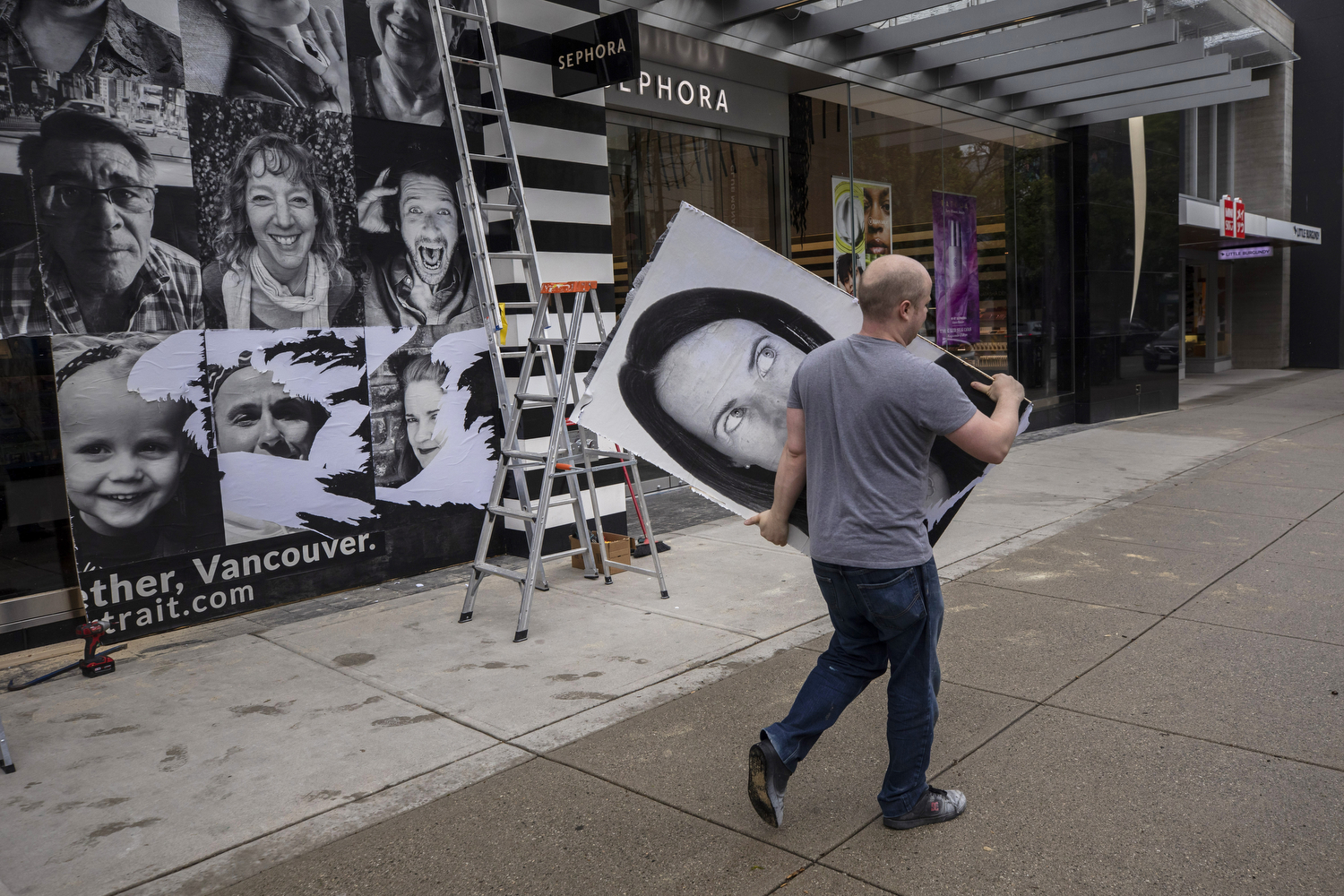 Workers take down plywood boards painted with murals covering up entrances of stores on Vancouver's Robson Street on May 11, 2020. B.C. entered Phase 2 of its pandemic restart program on May 19, allowing stores to reopen. (Ben Nelms/CBC Vancouver)