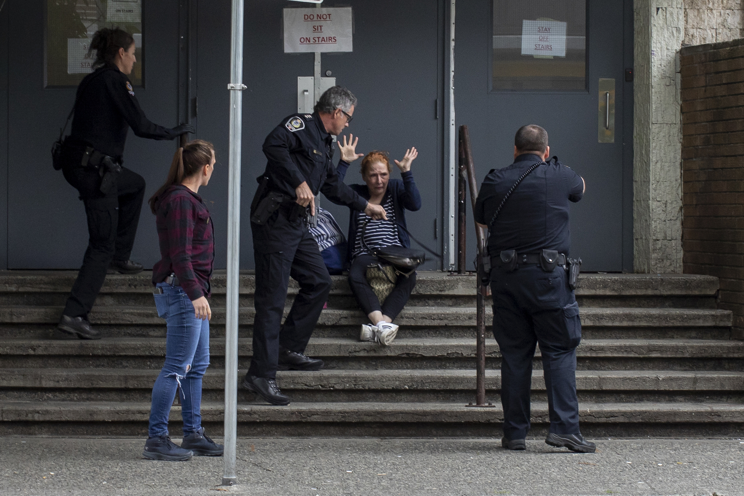 Vancouver police officers draw their guns while arresting a woman for reports of an illegal weapon in the Downtown Eastside of Vancouver on May 20, 2020. (Ben Nelms/CBC Vancouver)