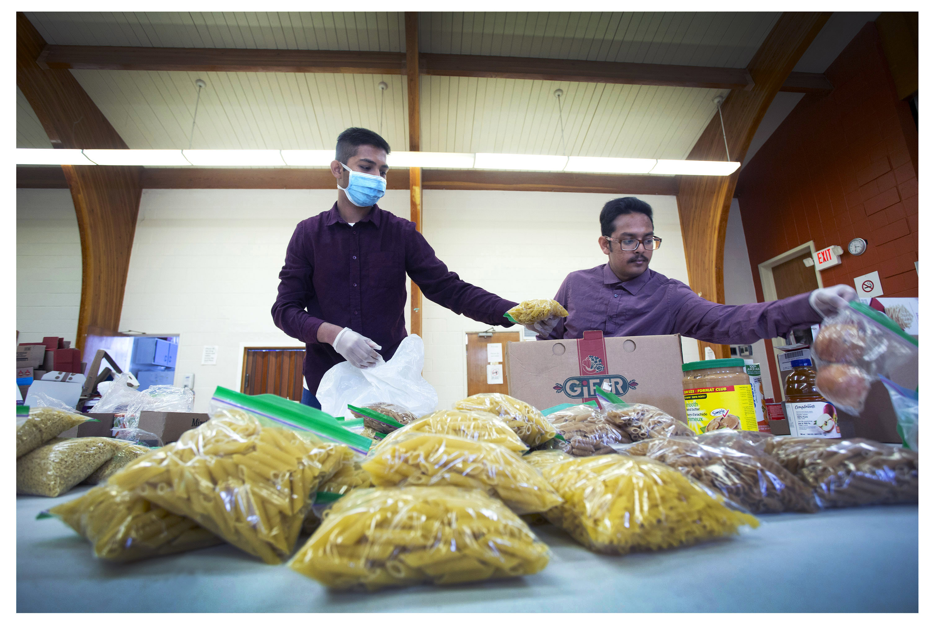Food NL volunteers Mahmudiel Islam Shourov and Adid Rahman prepare hampers for distribution. (Photo by Paul Daly)