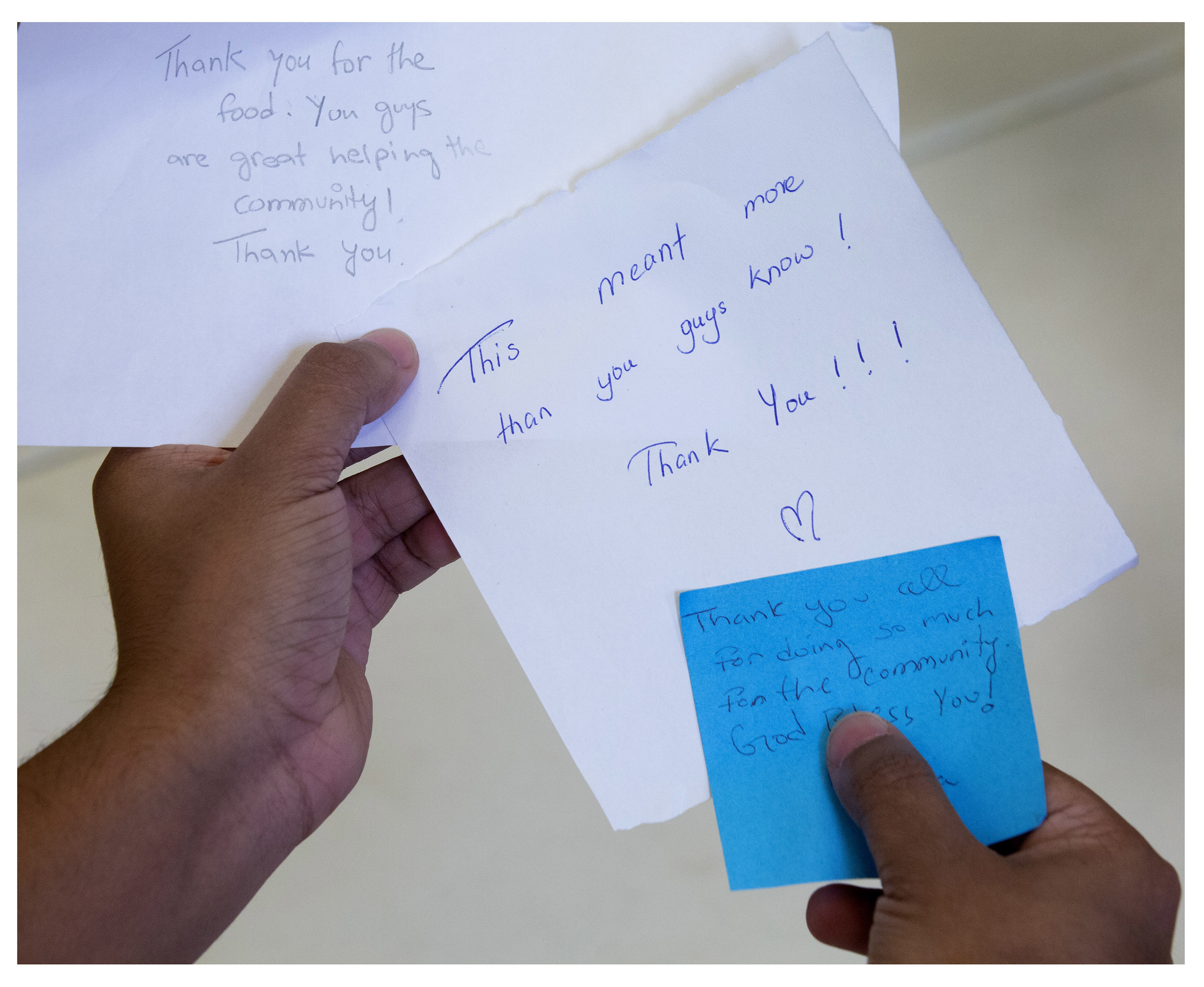 Adid Rahman, a business student at Memorial University, shows some of the notes that have been left for NL Eats volunteers when they deliver  food hampers in St. John's. The group has been using space at St. David's Presbyterian Church in St. John's.  (Photo by Paul Daly)