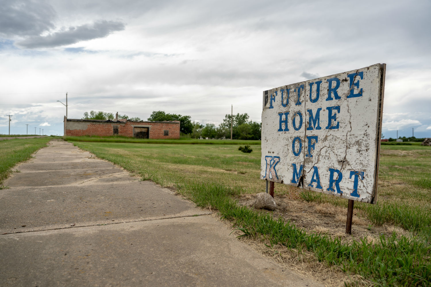 A sign in front of an empty field in Nemiskam, Alta., reads 'Future home of K-Mart.' (Vincent Bonnay/Radio-Canada)