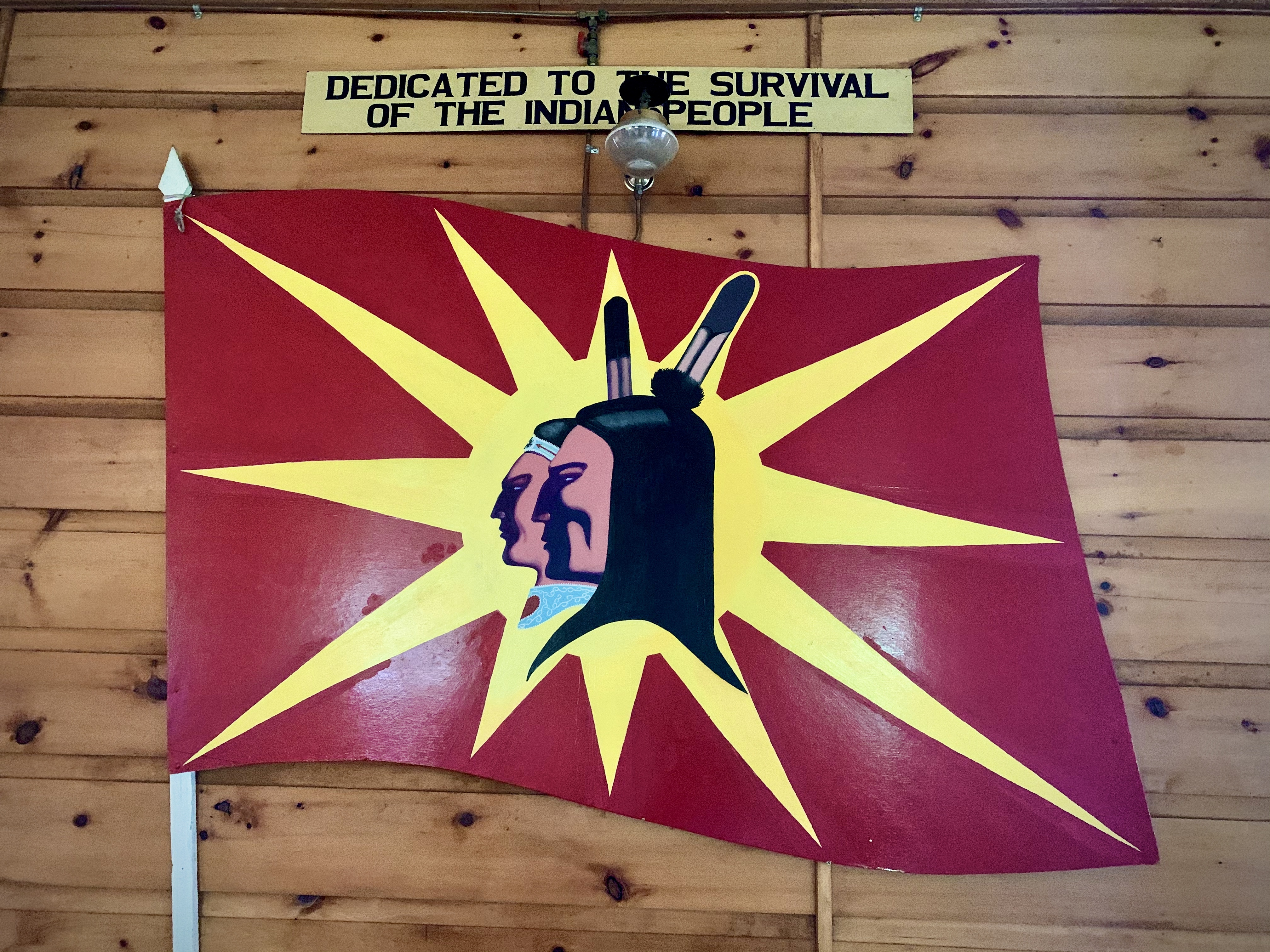 One of Hall's last paintings, of a new version of the warrior flag, hangs inside Kahnawake's Kanien'kehà:ka Nation Longhouse. (Jessica Deer/CBC)