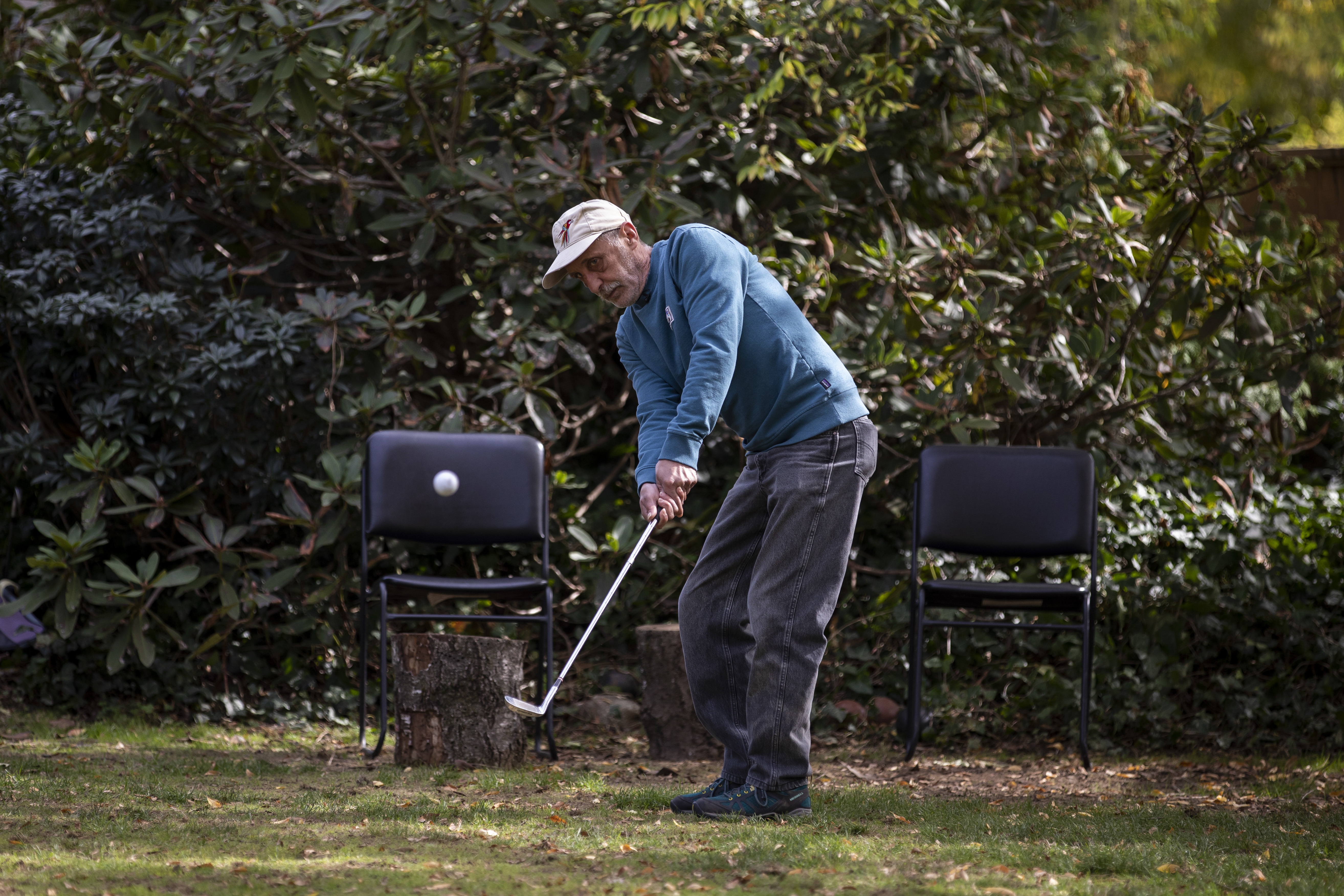 Charlie Smyth enjoys hitting the golf ball in his backyard now that he has settled into his housing unit. (Ben Nelms/CBC)