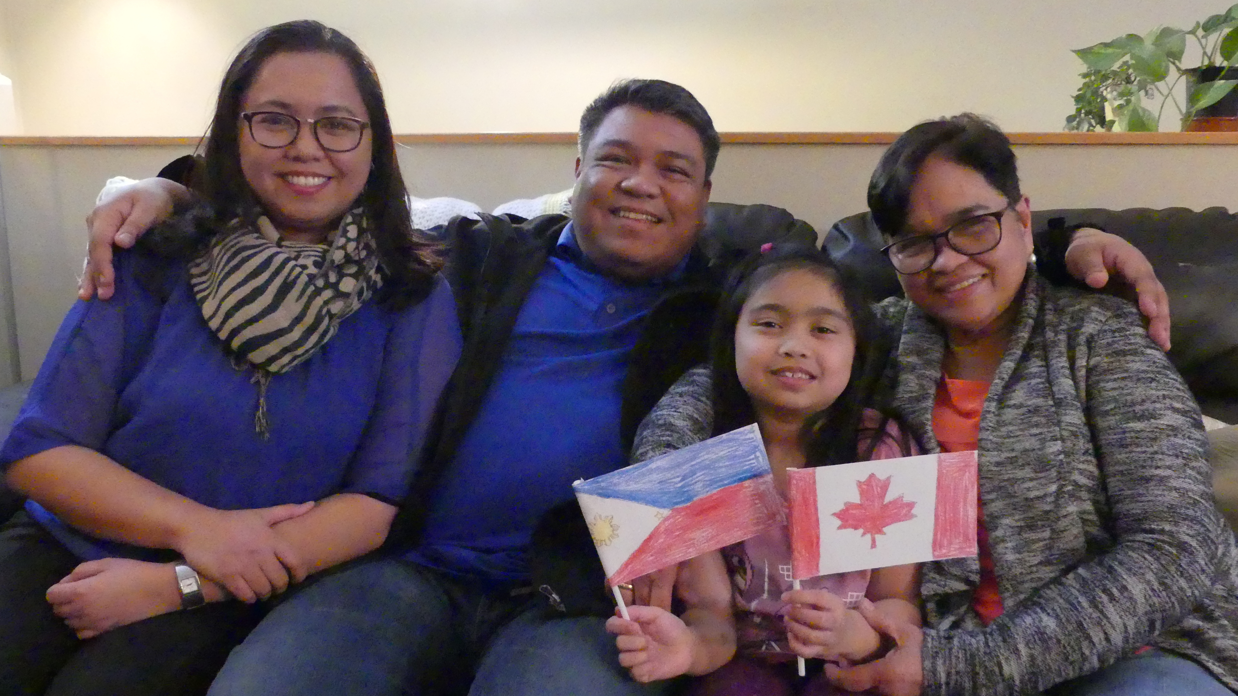 Peegy Ontong sits with her husband, Krispin, their seven-year-old daughter, Lexie, and Kris's mother, Angelita, in their shared home in Steinbach, Man. They've all lived together since Angelita moved to Canada, sponsored by Peegy, in 2017.