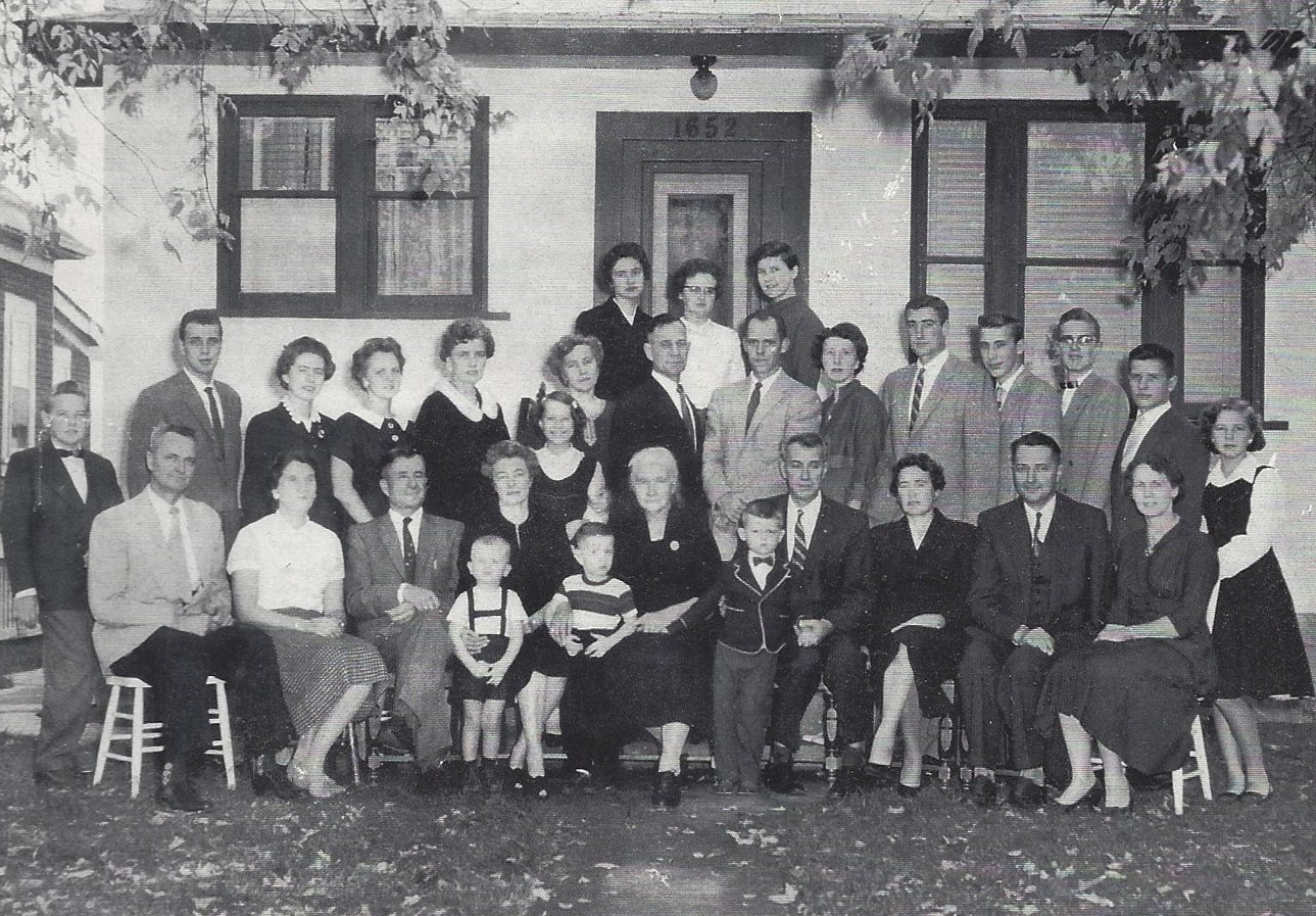 The Peters family gathers in front of the family home on Pacific Avenue W. in Winnipeg. Frank, seated at the far left, was seven years old when the family fled Russia. His son Robert is standing, centre, wearing a bowtie. The author's father, Henry Schroeder, stands in the middle row (second from the right), and Henry's mother, Melita, stands nears the centre (sixth from the left), with one of her daughters in front of her. (Robert Peters)
