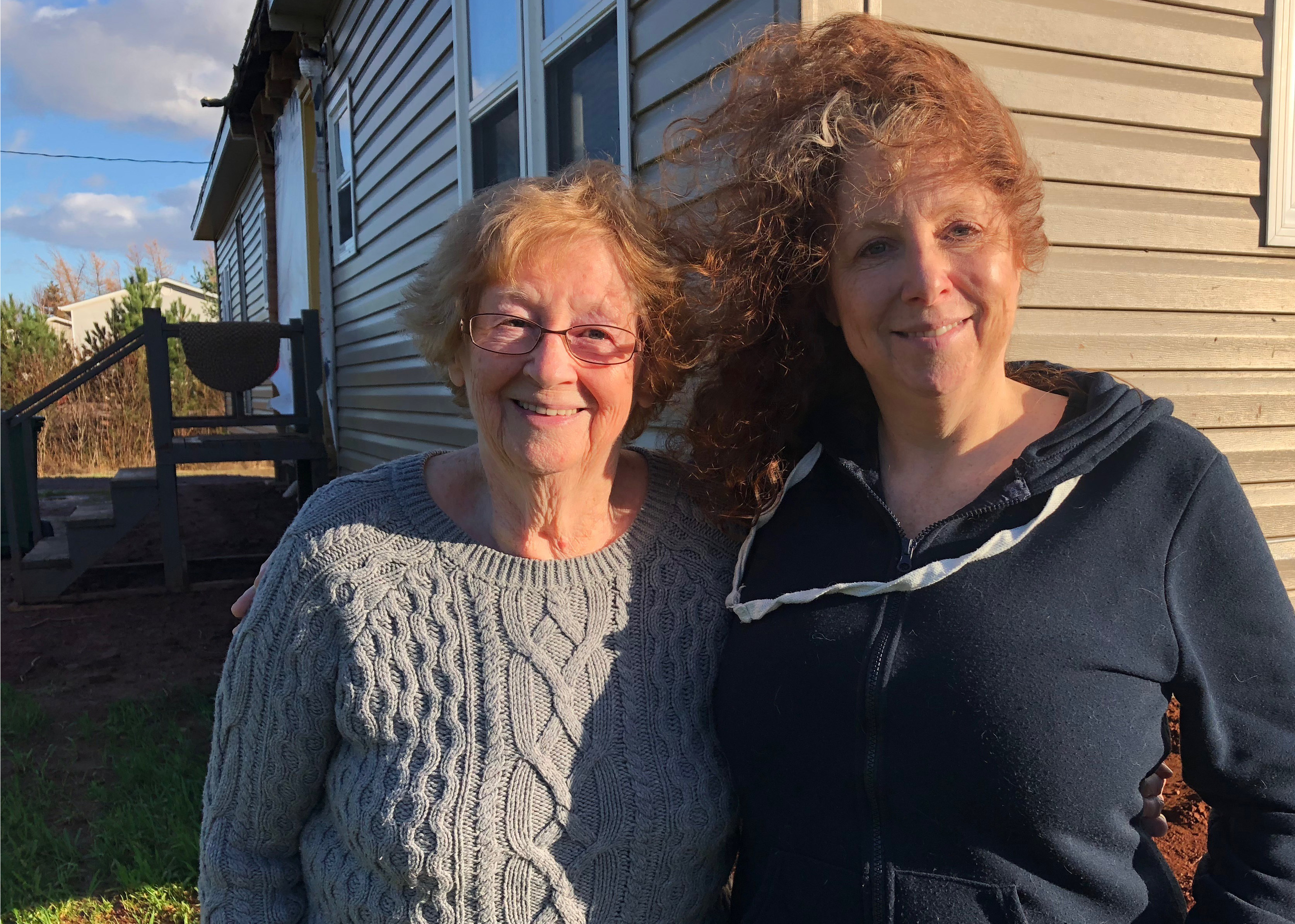 Pam Detlor (right) and her mother Jeannette Detlor outside their trailer which they moved to land just outside Summerside. Jeannette said she would have had to leave it if it wasn't for the help of her daughter. (Laura Meader/CBC)