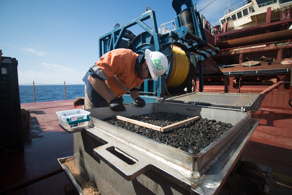 A worker examines polymetallic nodules as part of DeepGreen's ongoing evaluation of metals lying on the seabed in the Clipperton-Clarion Fracture Zone. (DeepGreen Metals Inc.)