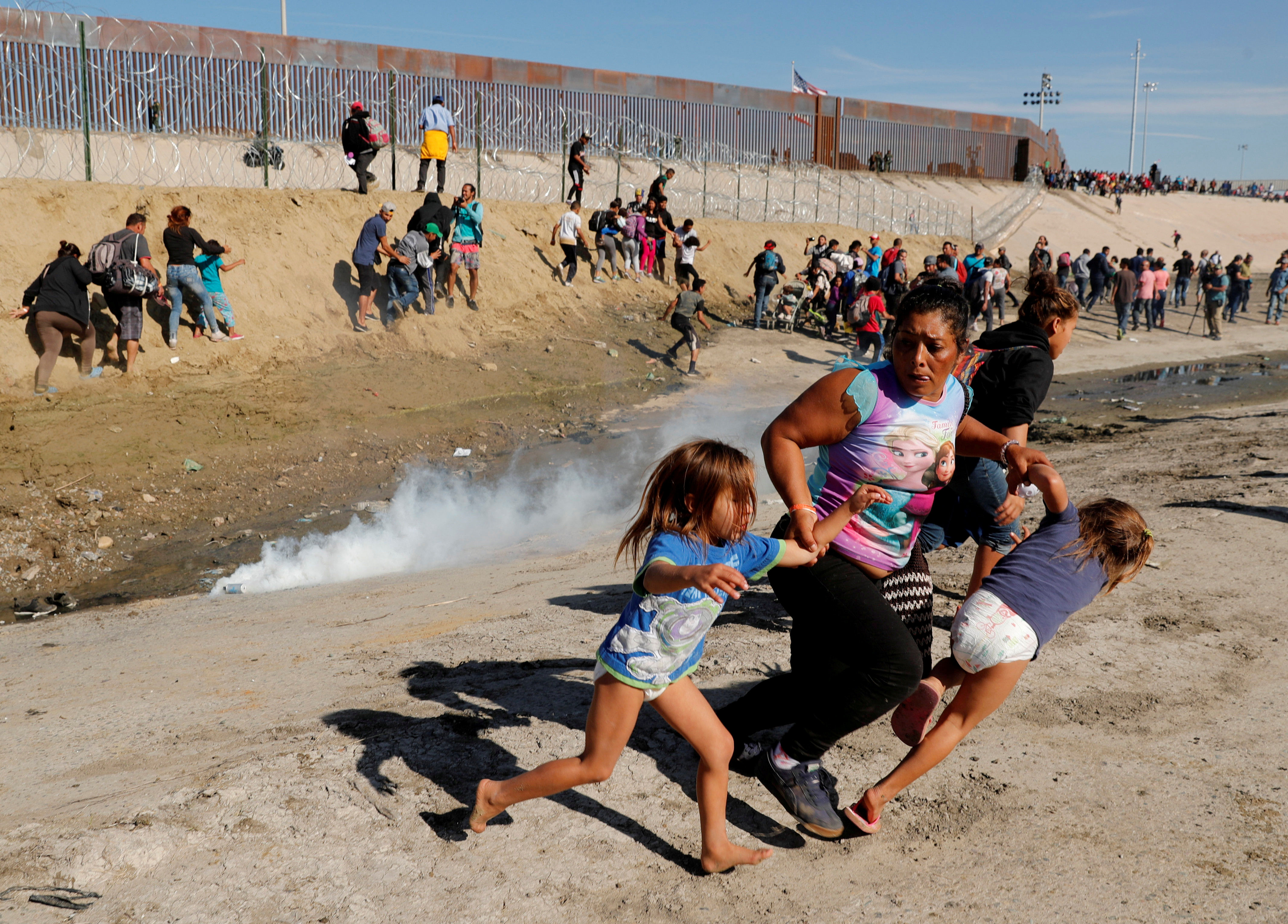 On Oct. 13, between 5,000 and 7,000 Hondurans and other Central Americans started walking toward the United States, hoping for asylum. They reached the U.S.-Mexico border in mid-November. In this photo, María Lila Meza Castro, a 39-year-old migrant woman from Honduras, runs from tear gas with her twin daughters in front of the border wall between the U.S. and Mexico. (Kim Kyung-Hoon/Reuters)