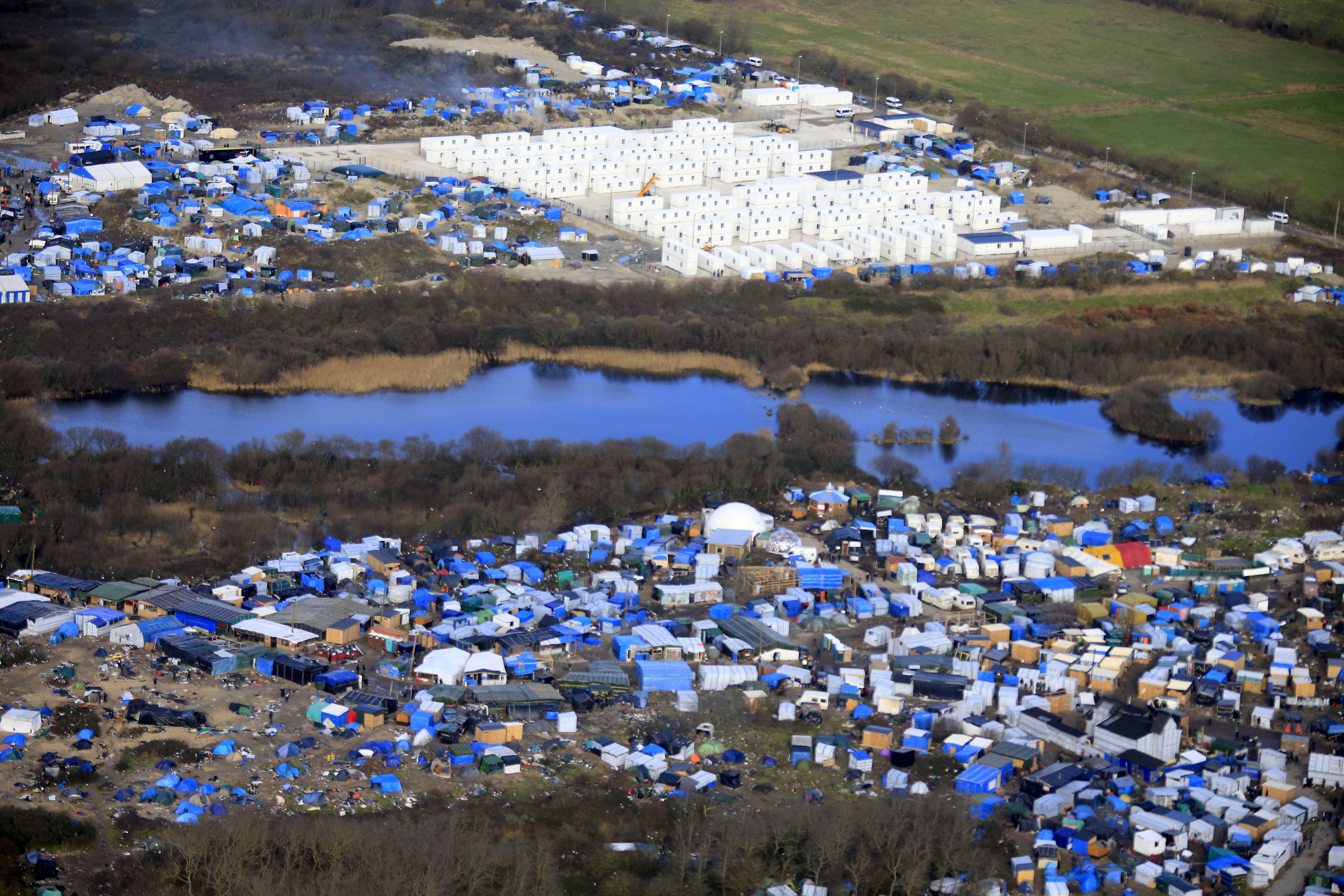 "Aerial view of a makeshift camp as containers (rear) are put into place to house several hundred migrants living in what is known as the ""Jungle,"" a squalid, sprawling camp in Calais, northern France, on January 17, 2016. (Pascal Rossignol/Reuters)"
