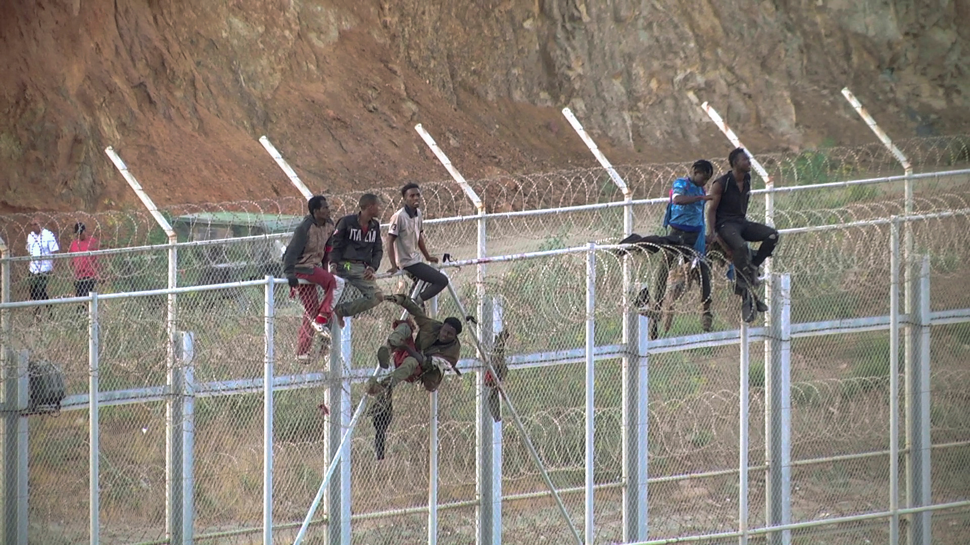 African migrants climb the border from Morocco to Ceuta, Spain, July 26, 2018, in this still image from video. (FARO TV via Reuters)