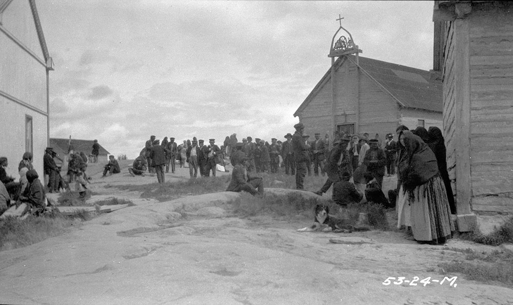 The community at Fort Rae gathering in front of the Roman Catholic mission church in 1924. Treaty documents were in several places entrusted to local priests, who lost or destroyed them during epidemics. (J. F. Moran / Department of Indian Affairs and Northern Development fonds / Library and Archives Canada / a102611-v8)