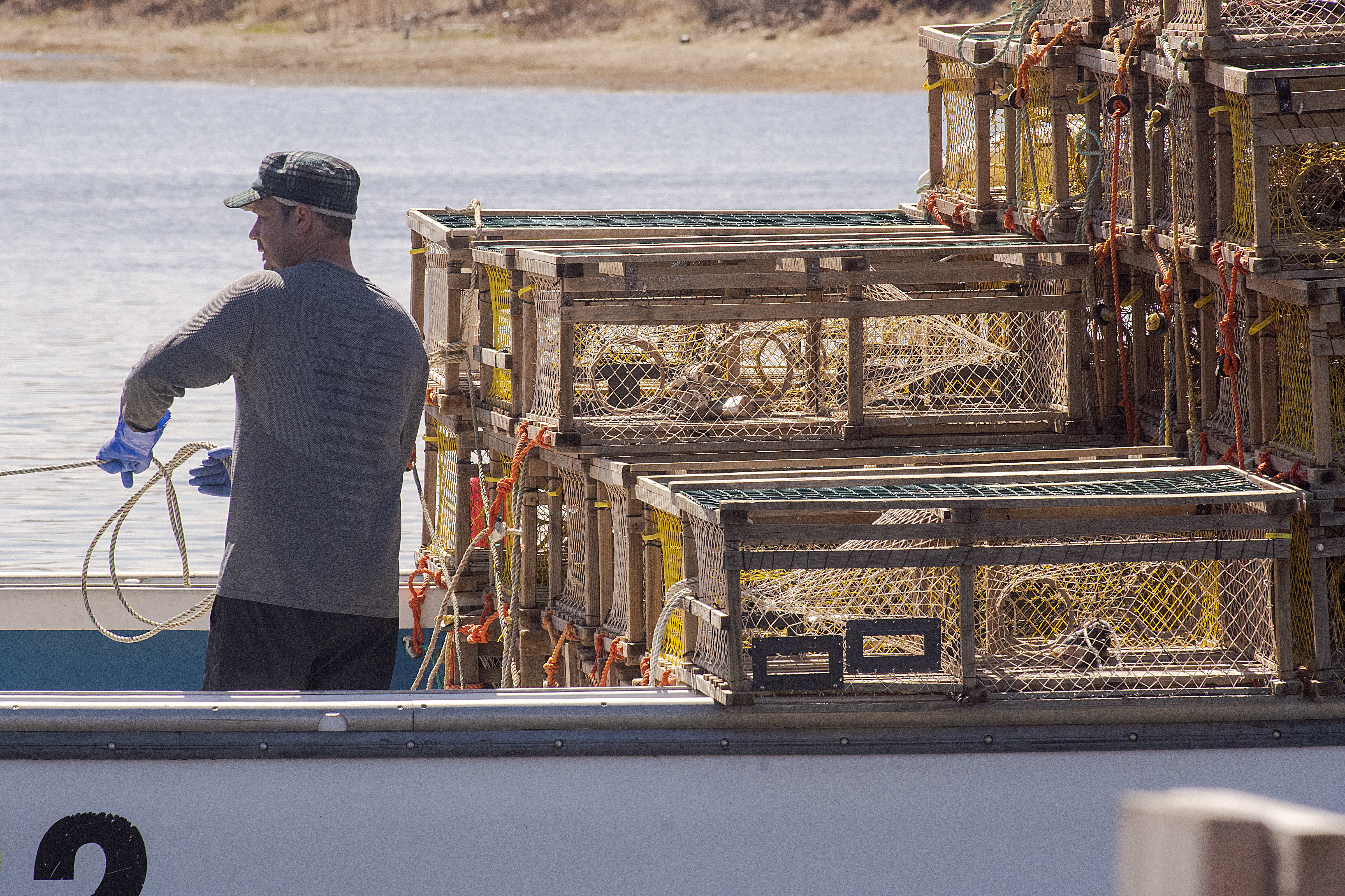 The ropes attached to the traps have to be tied in such a way it is difficult for anyone to get their feet tangled. Each trap weighs upwards of 60 pounds which could easily drag an unwary deckhand overboard. (Brian McInnis/CBC)