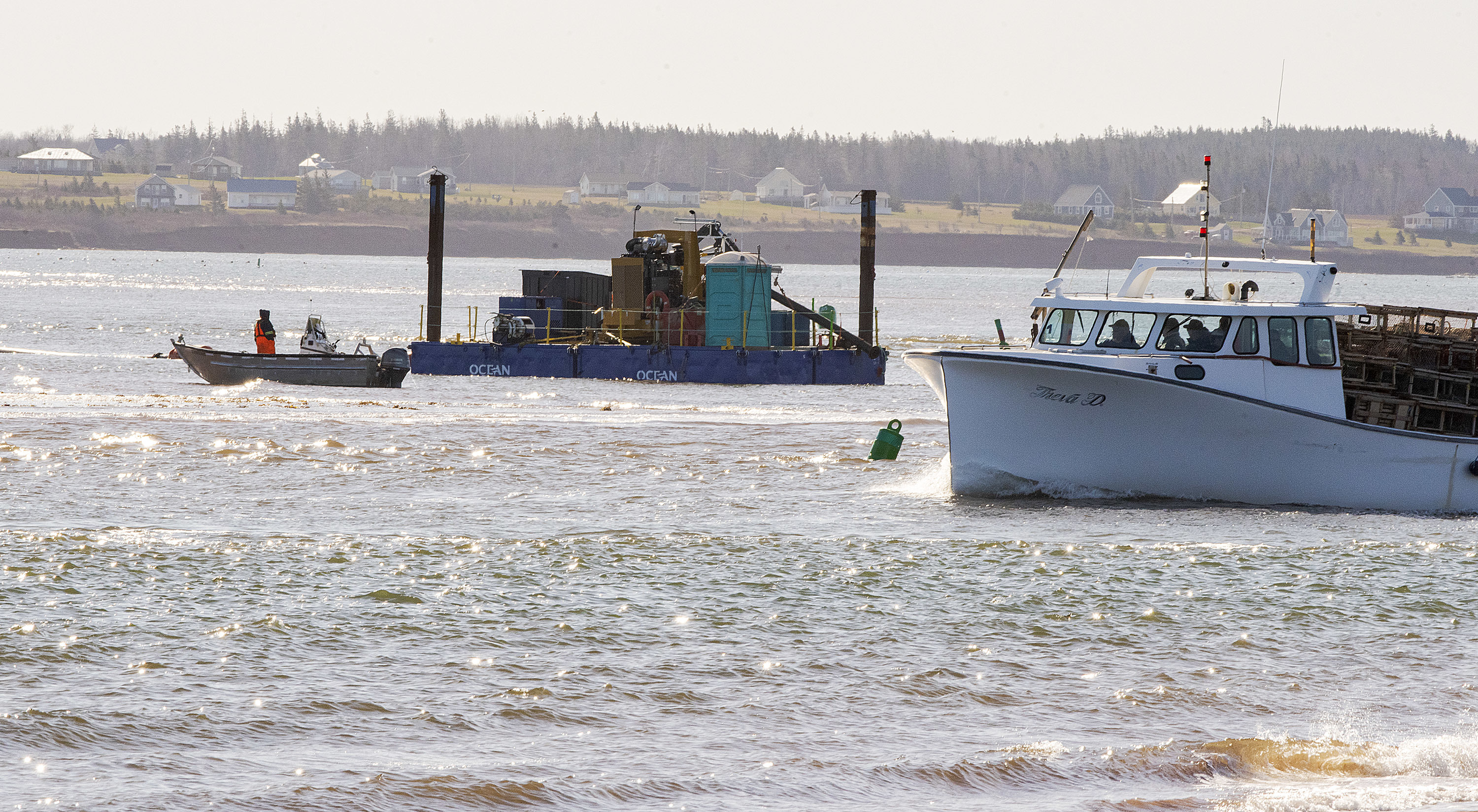 The Freda V sails past the dredger that is clearing the mouth of Malpeque Harbour. The harbour tends to get filled with sand and the dredger needs to clear the channel for the safety of the fishermen heading to and from the lobster grounds. (Brian McInnis/CBC)