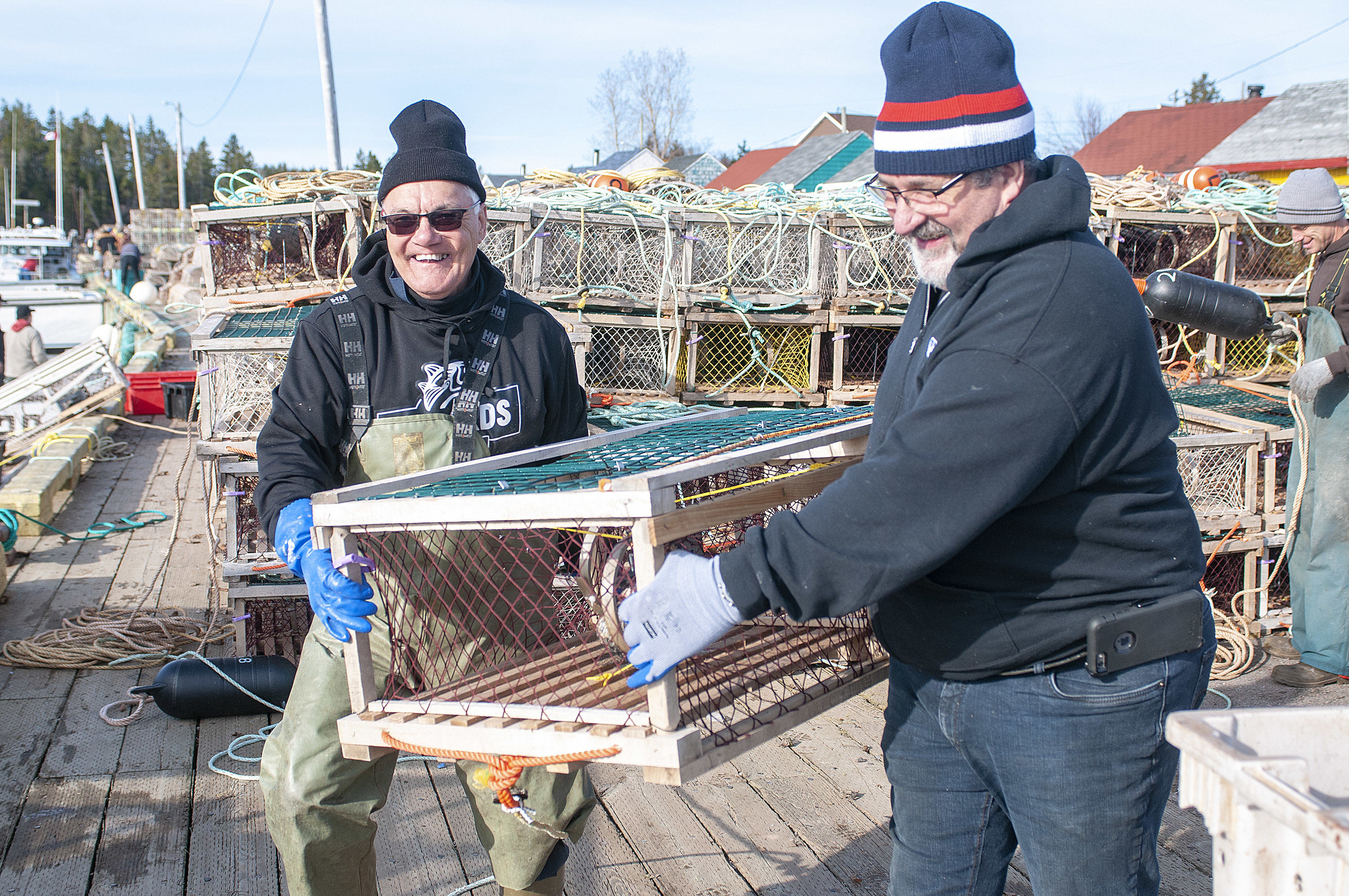 Captain Alfred Gallant, left, of Mister In-Between and Larry Court, load traps onto the boat after setting their first load earlier in the morning. Each boat is allowed approximately 300 traps and they split those between two runs. (Brian McInnis)