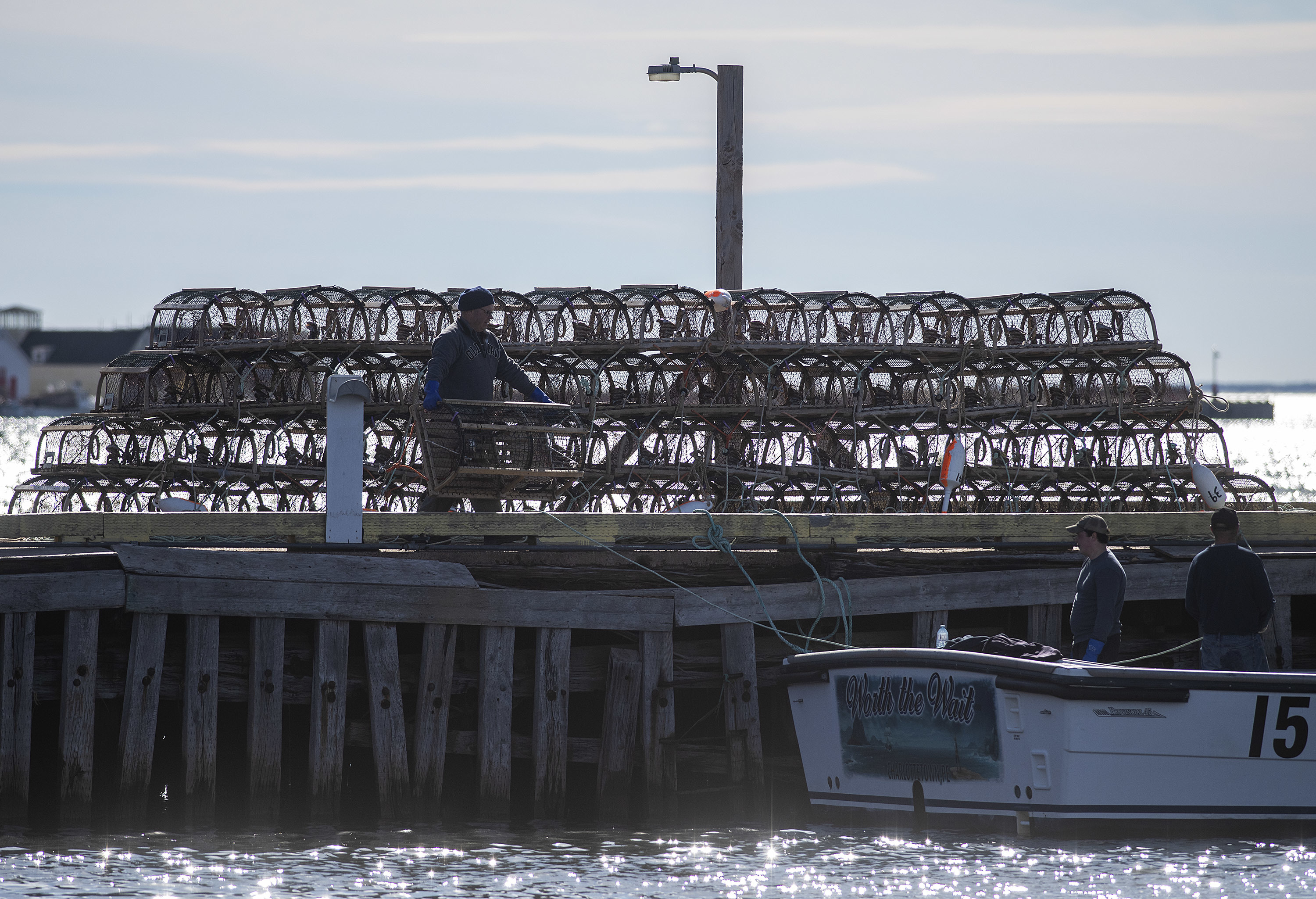 Traps are silhouetted on the wharf as fishermen bait them and load them onto a boat. (Brian McInnis)