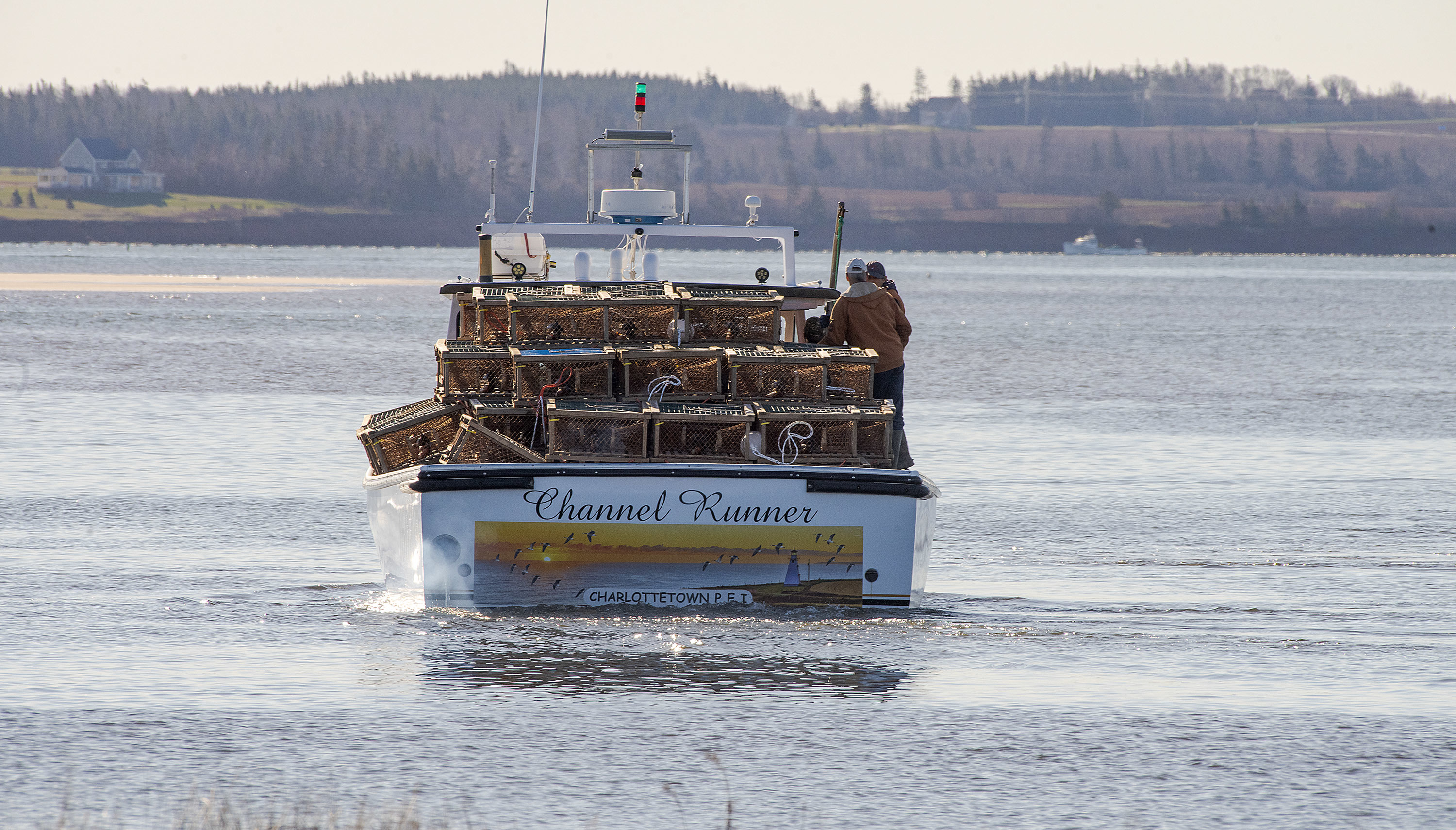 The Channel Runner, loaded with approximately 150 lobster traps, heads toward the Malpeque Harbour channel. (Brian McInnis/CBC)