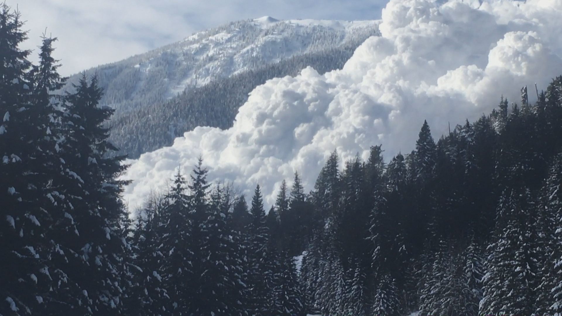 The snow comes roaring down the mountainside after the team triggers an avalanche. (Ministry of Transportation/Video)