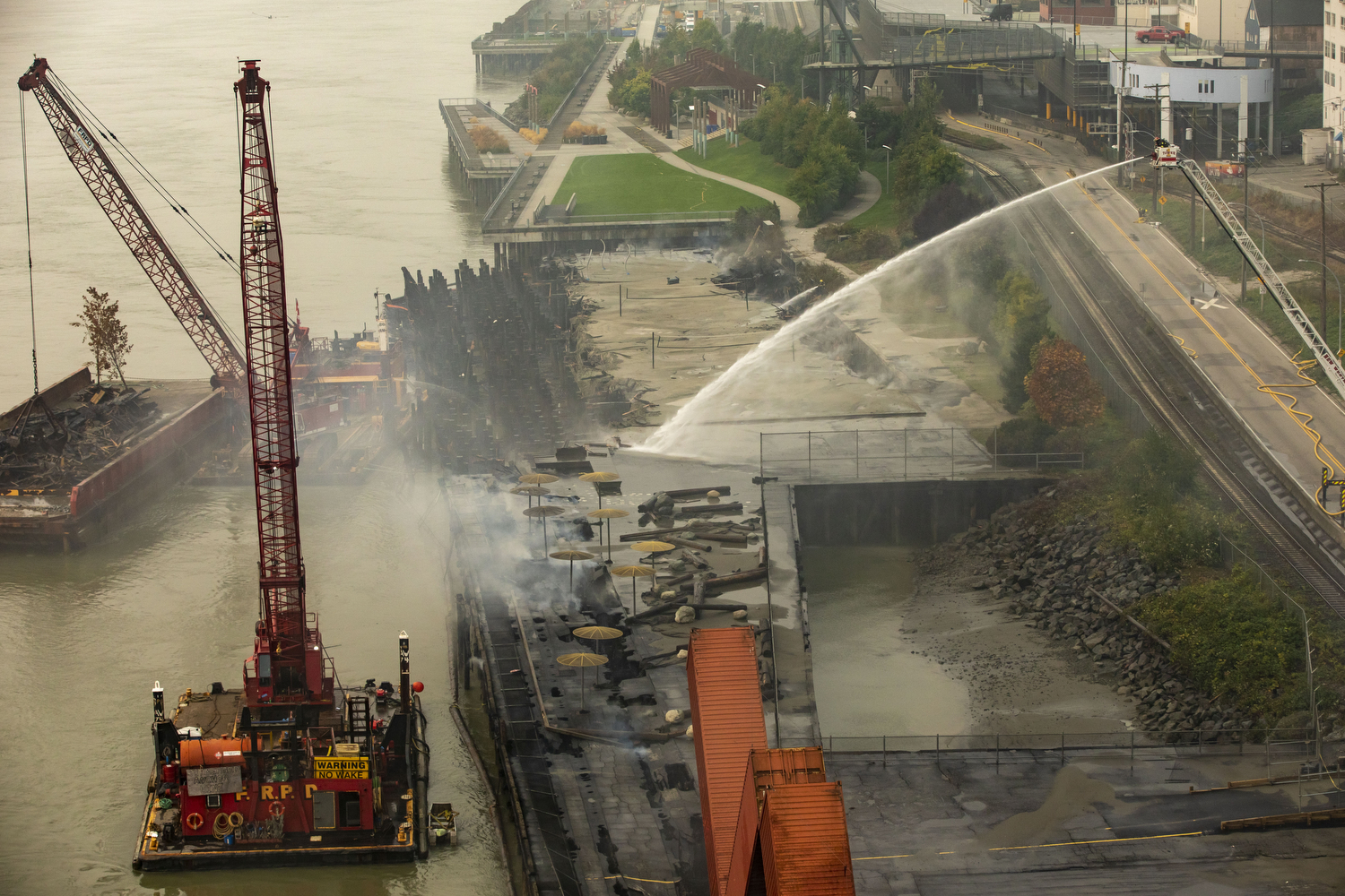 Fire crews work to put out a fire under the historic New Westminster Pier in New Westminster, B.C., on Sept. 16, 2020. It continued to smoulder for 11 days. Westminster Pier Park is expected to re-open in February 2021. (Ben Nelms/CBC Vancouver)