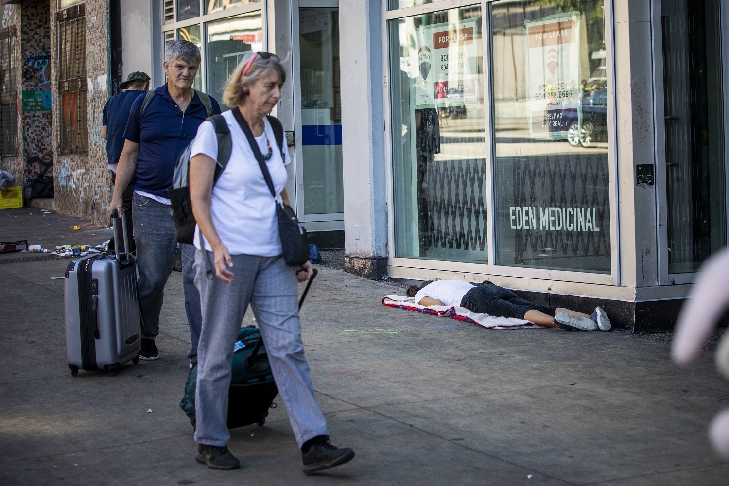A man and woman walk past a woman lying on the ground along Hastings Street in Vancouver, British Columbia on Friday, September 6, 2019. (Ben Nelms/CBC)