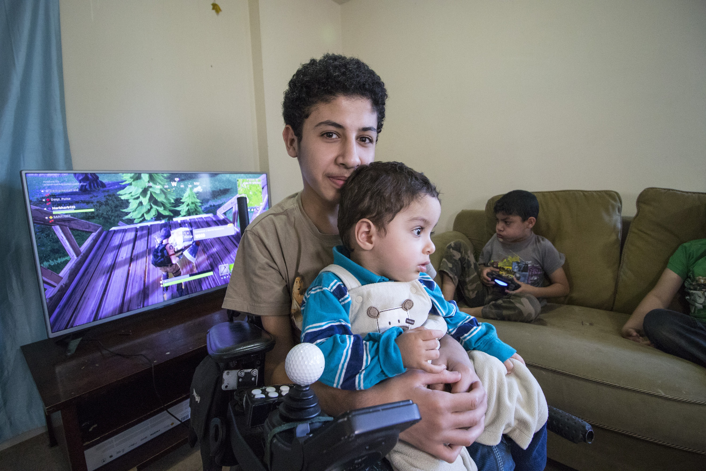 Maher holds Mias, who has also been diagnosed with muscular dystrophy. Younes is playing video games. (Dave Irish/CBC)