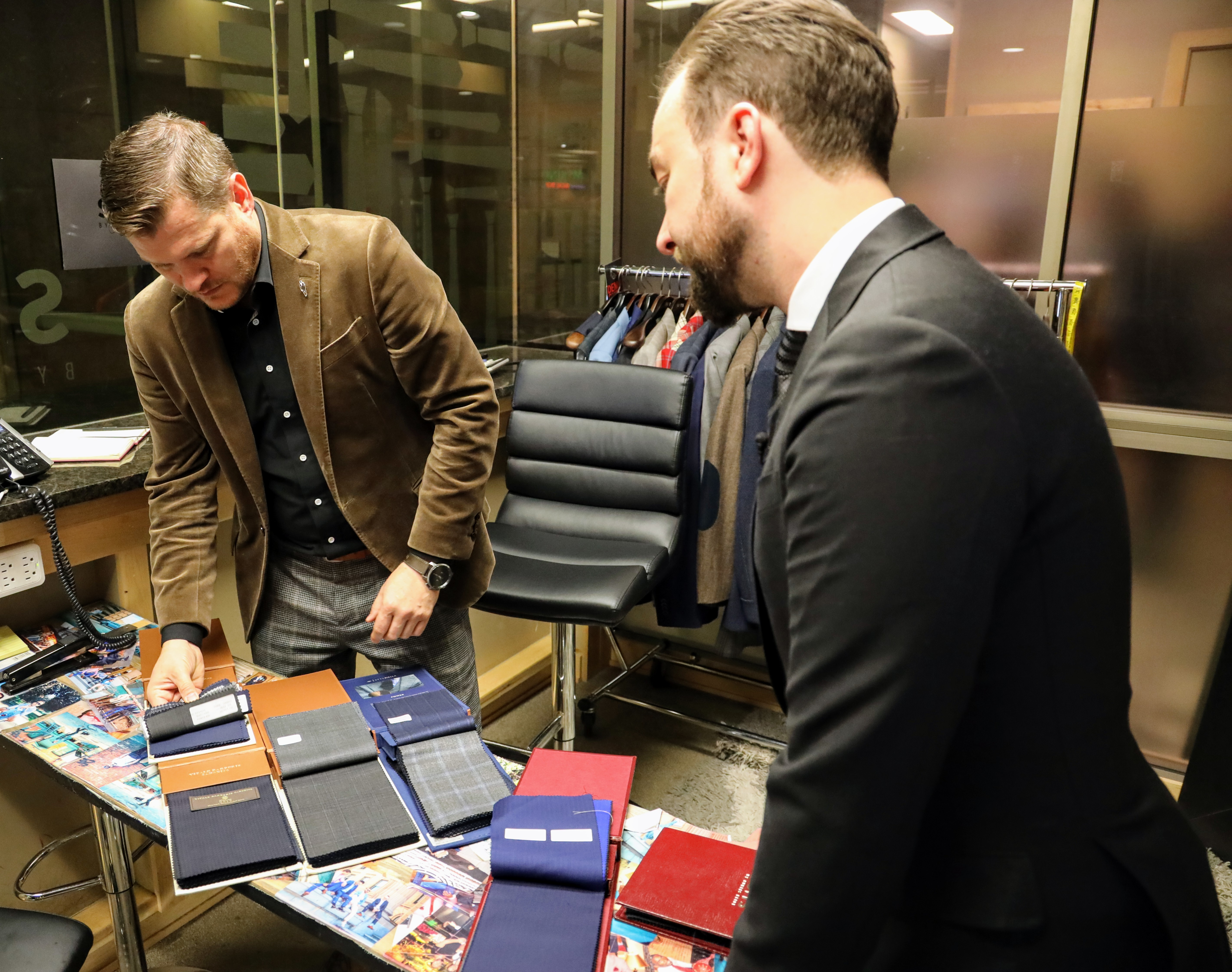 Farmer and salesman Jared Berry go through the many options for their bespoke suits.